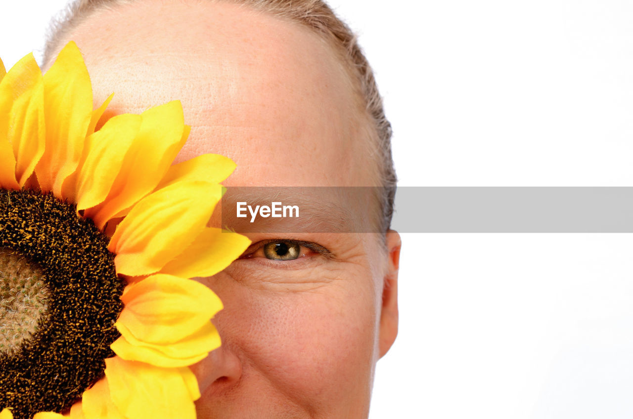 human body part, flower, flowering plant, studio shot, portrait, yellow, body part, close-up, human face, one person, headshot, white background, petal, freshness, flower head, beauty in nature, plant, human head, hairstyle, sunflower, human hair, softness