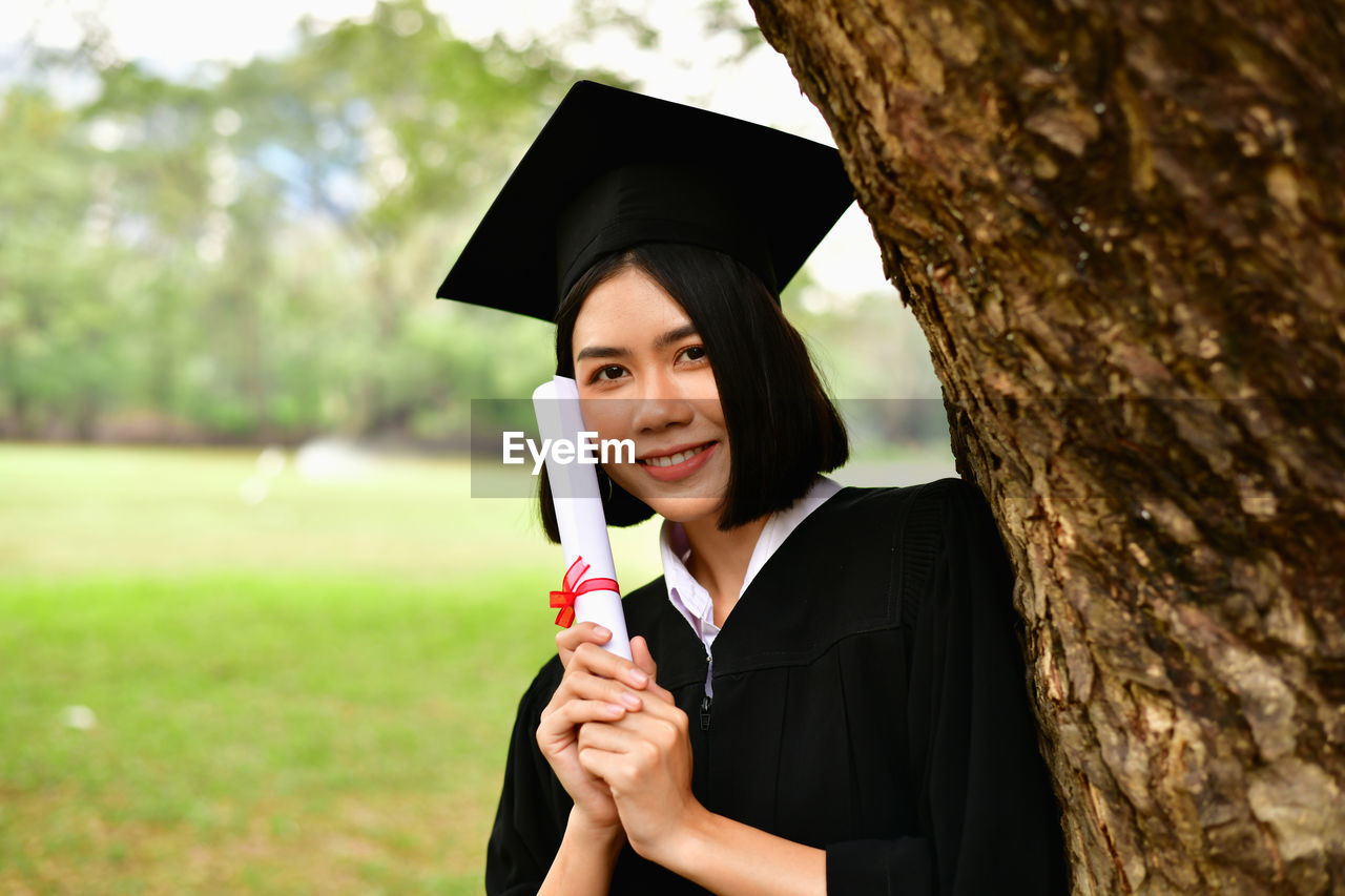 real people, young adult, one person, tree trunk, trunk, portrait, holding, plant, graduation gown, graduation, front view, day, achievement, tree, young women, lifestyles, focus on foreground, mortarboard, outdoors