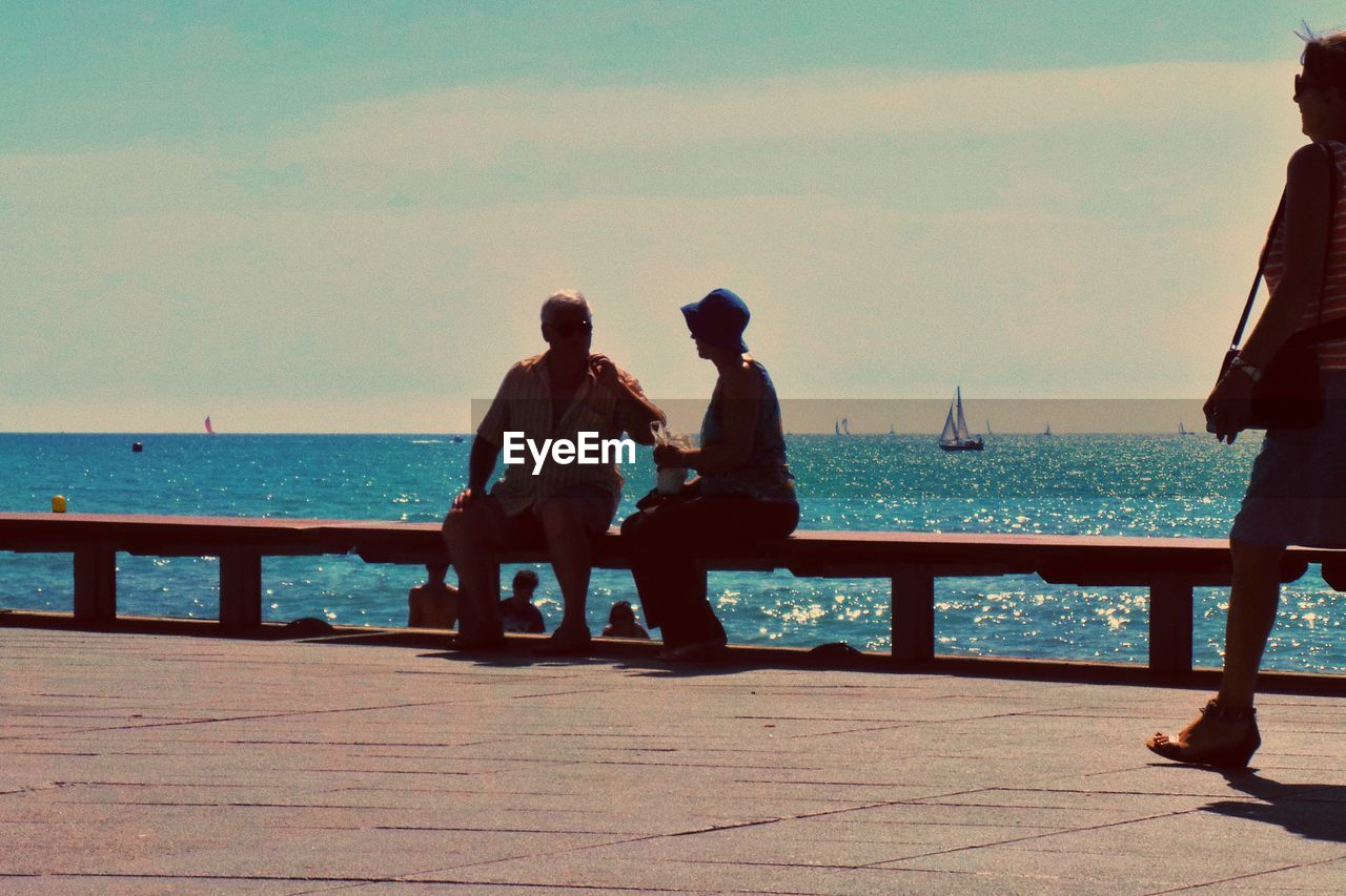 water, sea, sky, two people, men, real people, nature, sitting, leisure activity, horizon, lifestyles, horizon over water, togetherness, people, beauty in nature, scenics - nature, railing, day, adult, couple - relationship, outdoors, looking at view