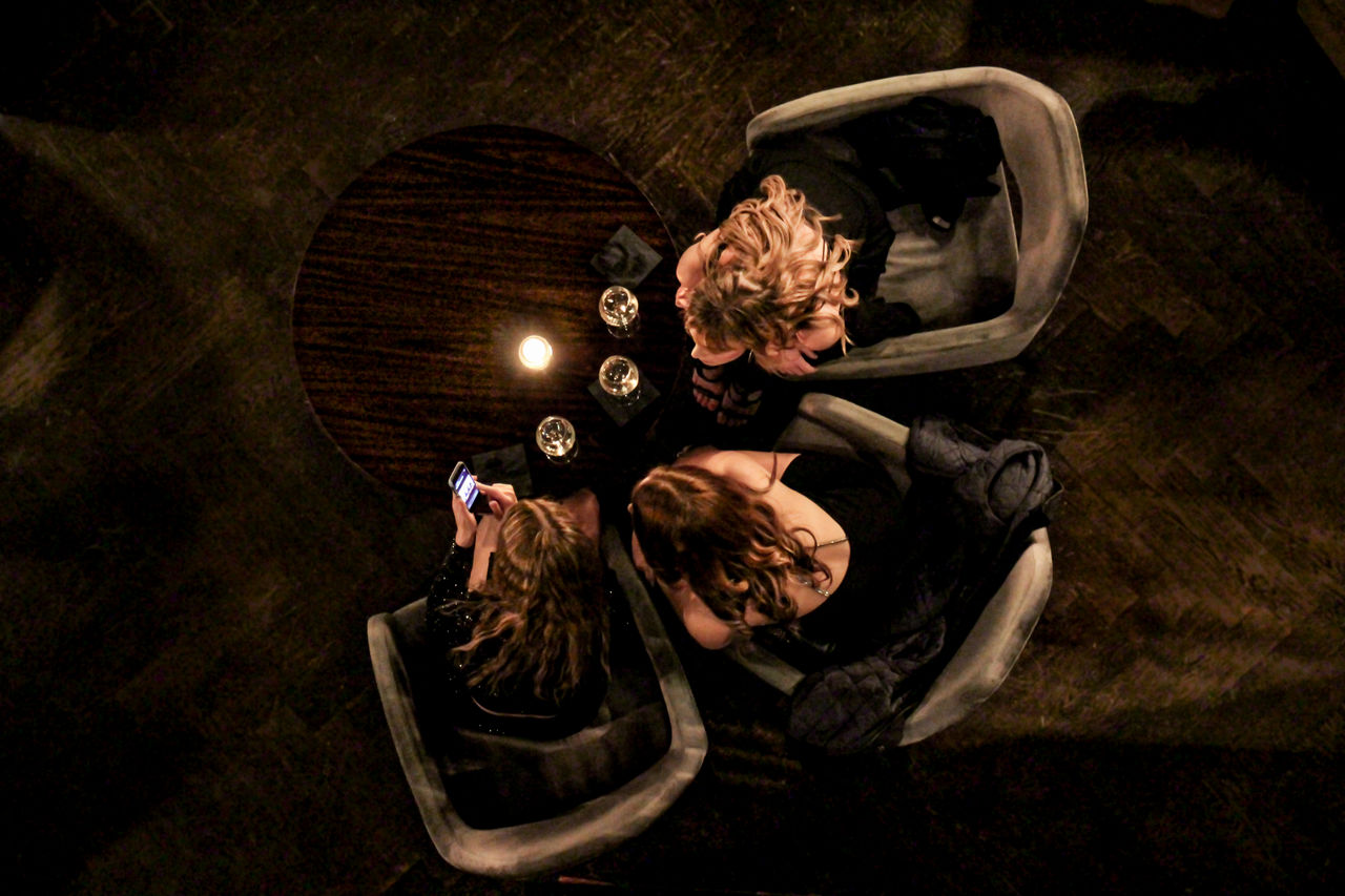HIGH ANGLE VIEW OF COUPLE SITTING AT THE DARK