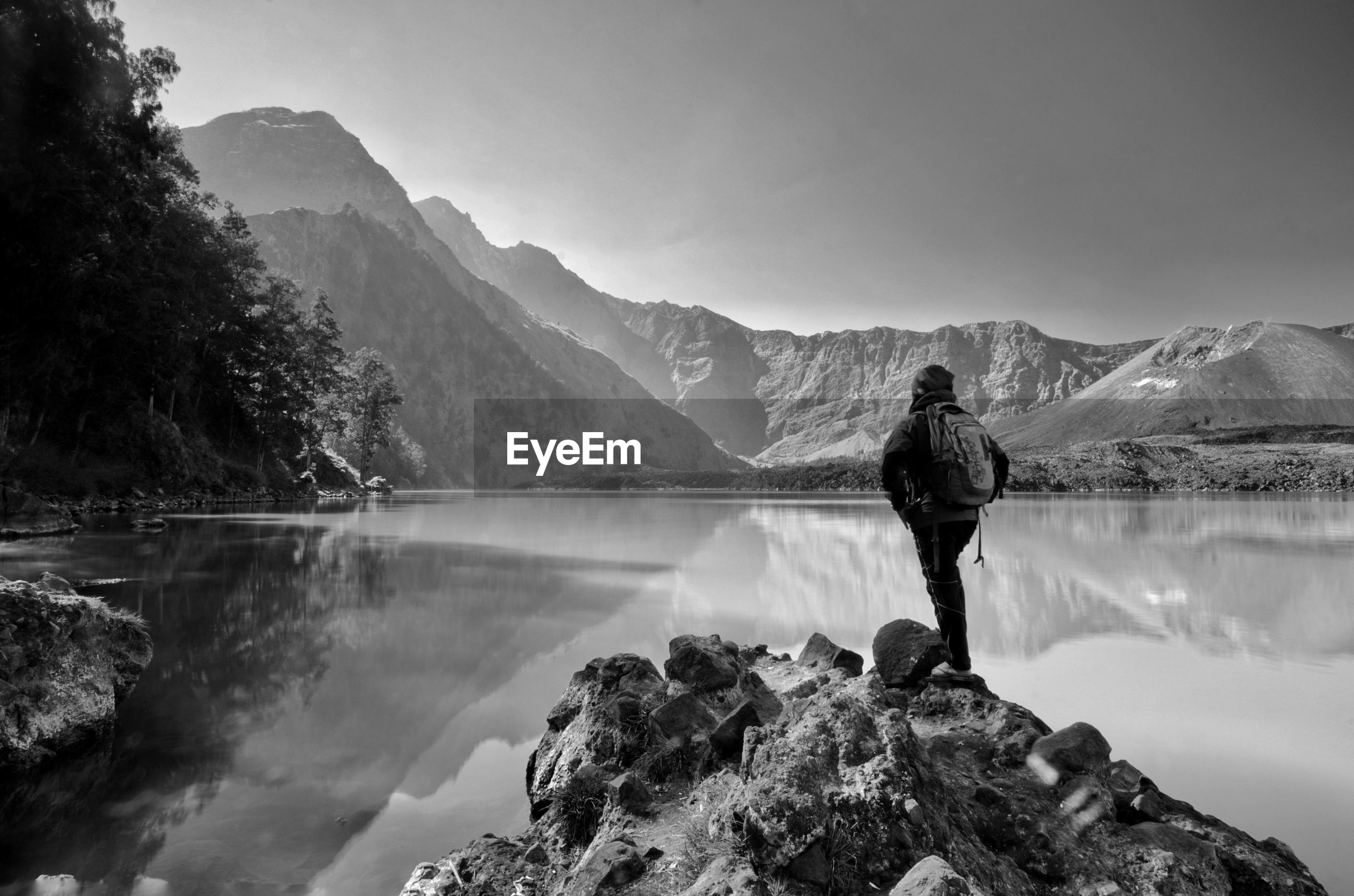 Rear view of man standing on rock at lakeshore against mountains