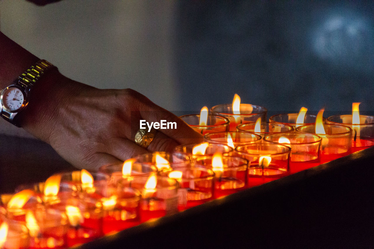Cropped Hand Of Woman Arranging Lit Tea Lights In Darkroom