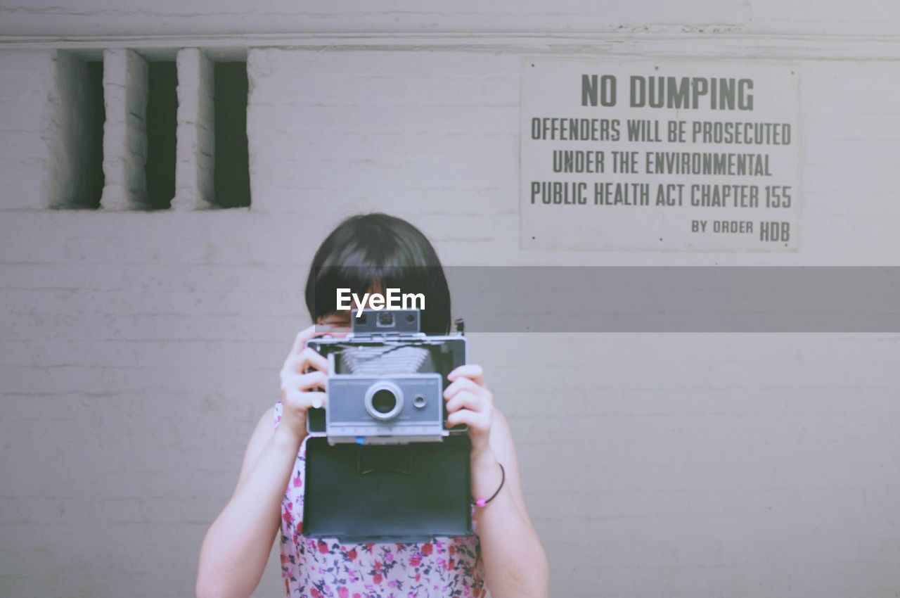 Woman Photographing From Camera While Standing Against Wall With Text