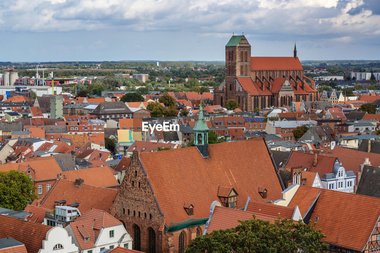 building exterior, architecture, built structure, city, building, residential district, roof, cityscape, sky, crowd, high angle view, cloud - sky, crowded, house, nature, day, town, community, outdoors, townscape, roof tile, gothic style
