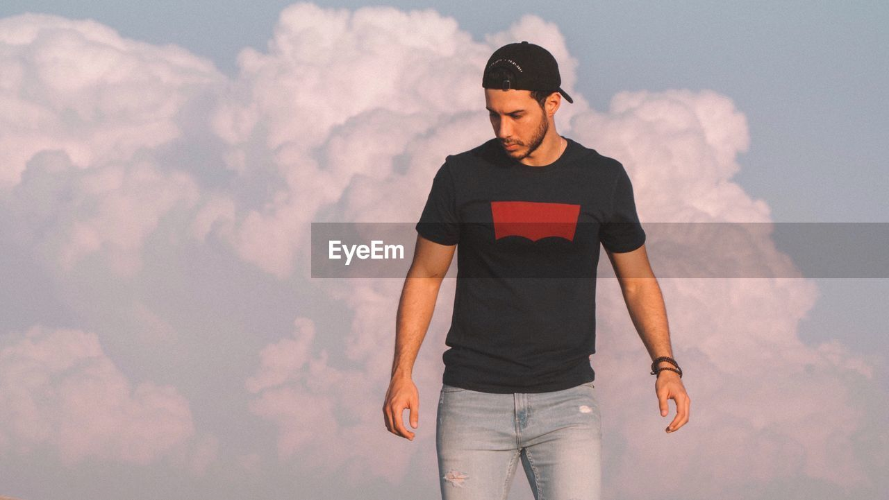 cloud - sky, three quarter length, casual clothing, front view, one person, sky, standing, young adult, nature, real people, young men, looking, leisure activity, lifestyles, day, outdoors, looking away, young women, contemplation, teenager, jeans