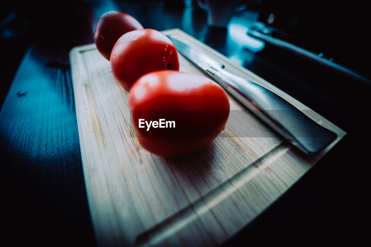 food, healthy eating, food and drink, red, wellbeing, table, fruit, still life, indoors, freshness, close-up, wood - material, vegetable, tomato, no people, selective focus, high angle view, cutting board, kitchen knife, focus on foreground, tray