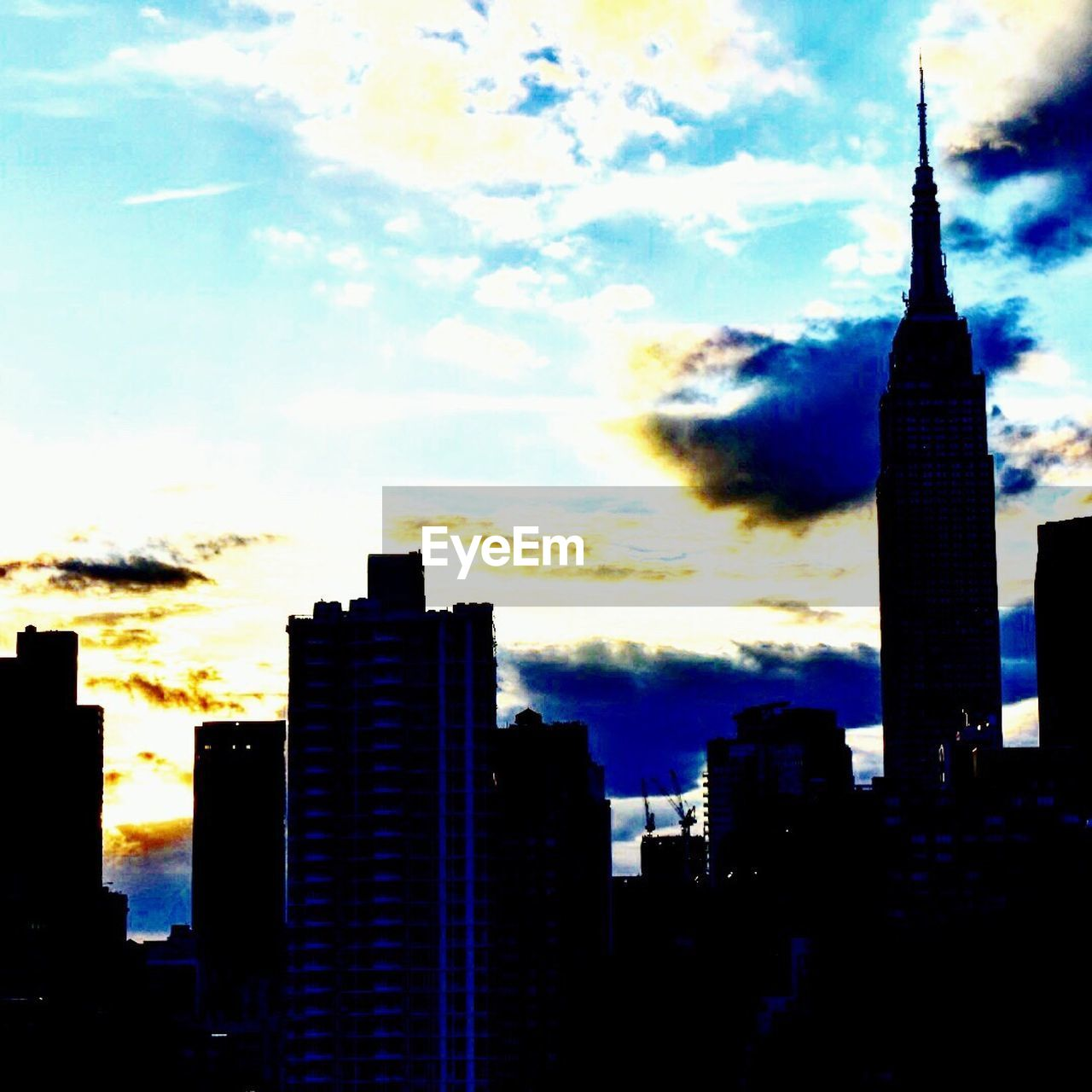 architecture, building exterior, built structure, skyscraper, tall - high, sky, city, tower, modern, cloud - sky, sunset, no people, cityscape, travel destinations, silhouette, outdoors, tall, urban skyline, nature, day