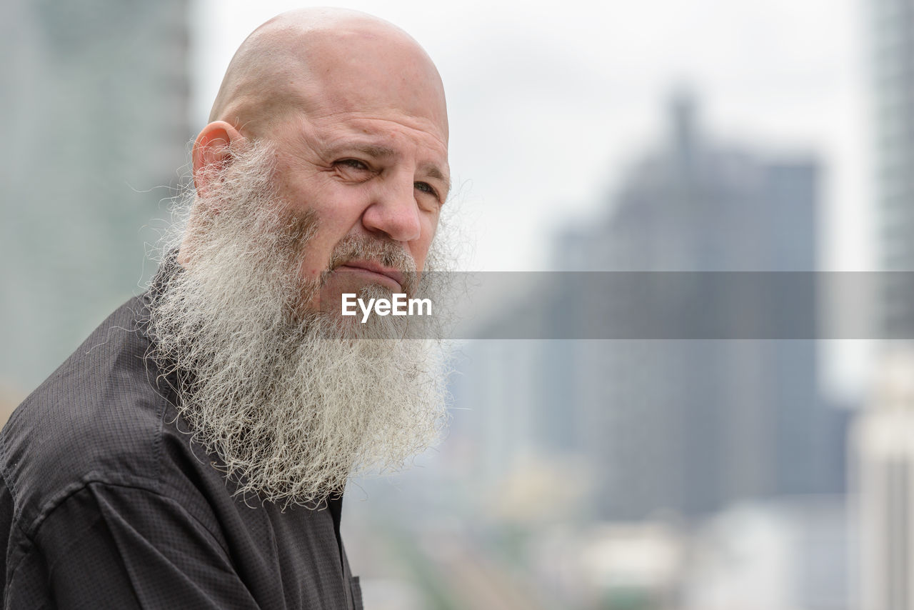 Close-up of man with beard looking away outdoors