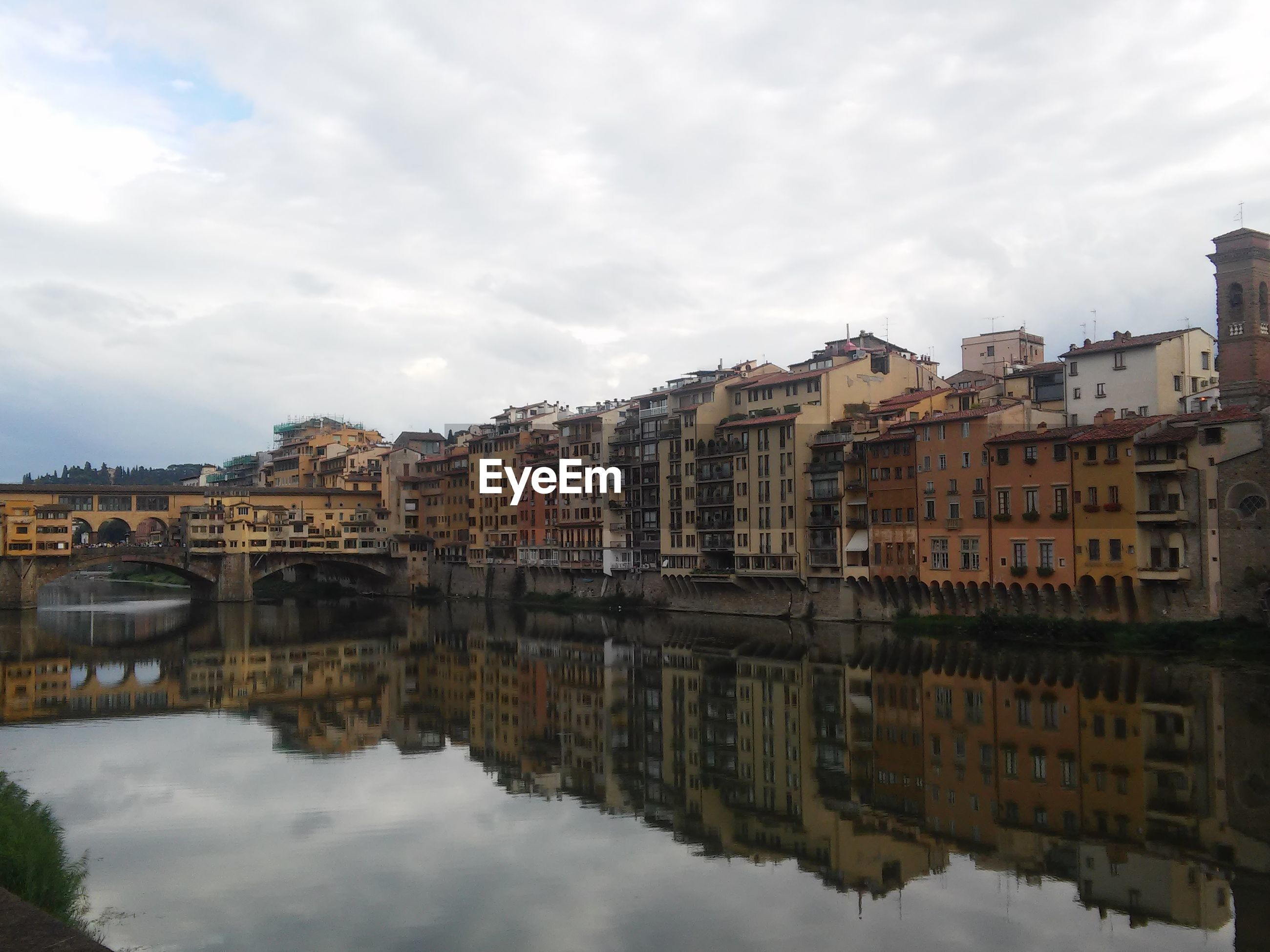 Reflection of buildings on river against sky in city