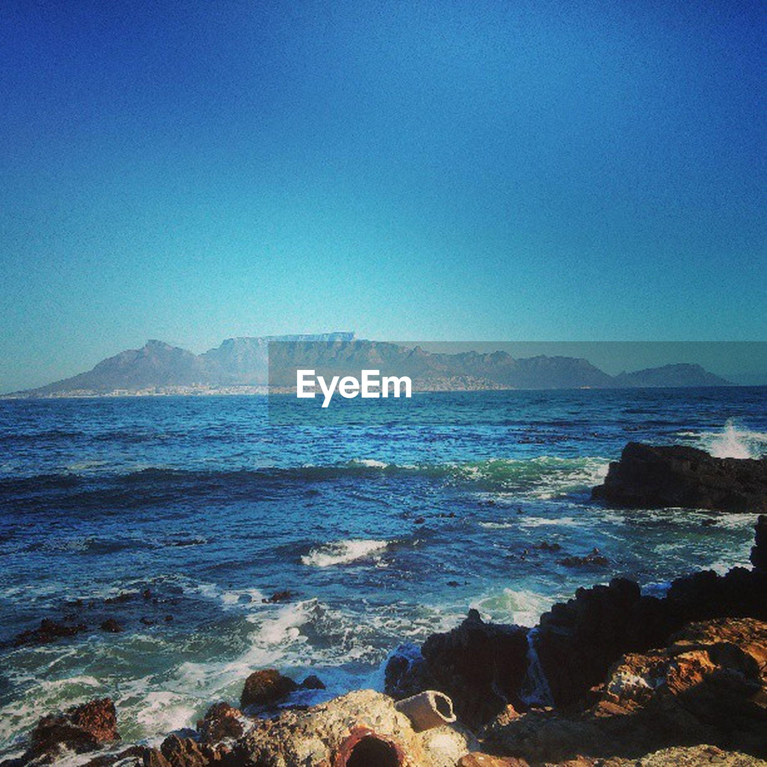 water, clear sky, sea, scenics, blue, tranquil scene, beauty in nature, copy space, mountain, tranquility, nature, rock - object, idyllic, rock formation, coastline, wave, shore, beach, mountain range, non-urban scene