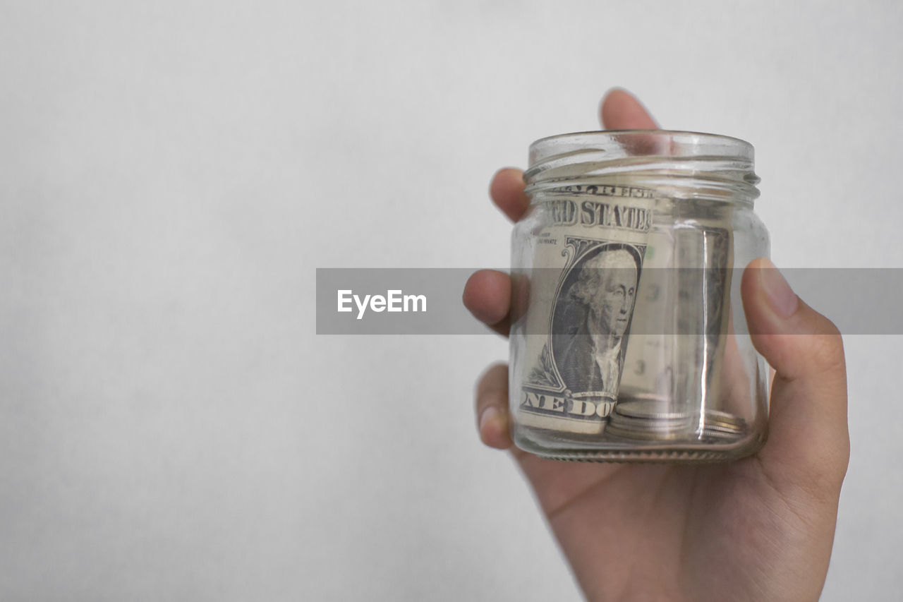 Close-up of hand holding money in jar against white background