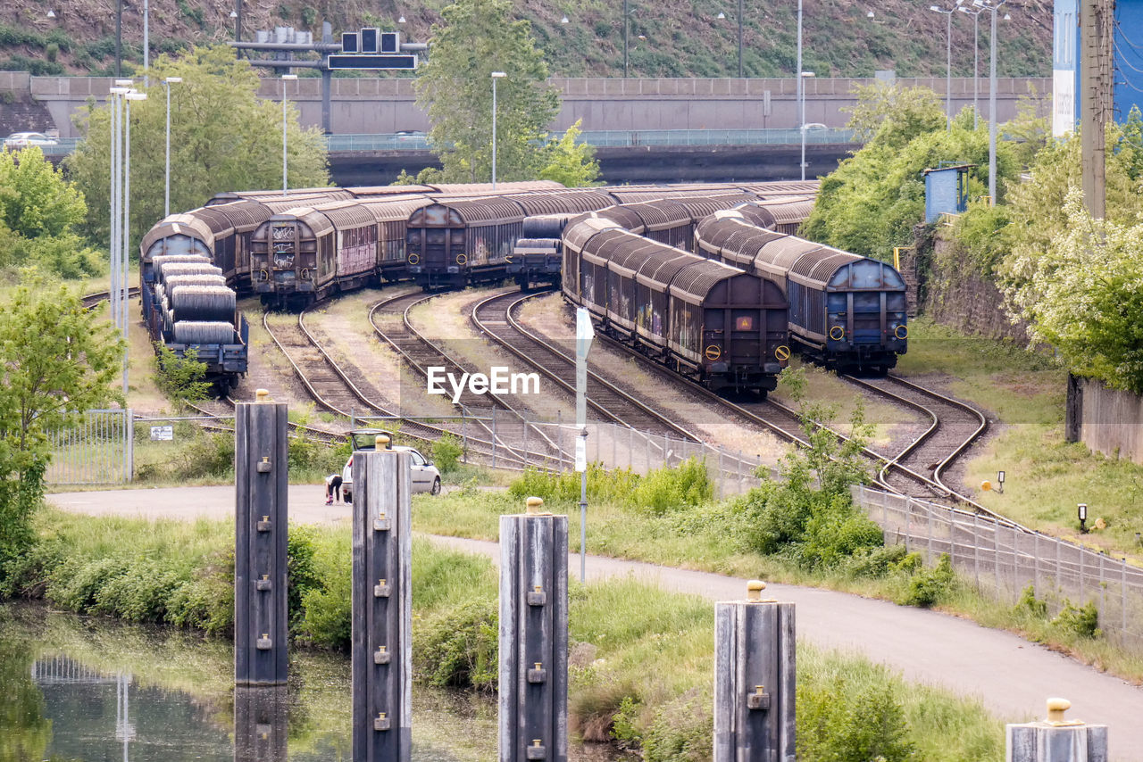 train, transportation, rail transportation, mode of transportation, train - vehicle, plant, tree, land vehicle, day, track, railroad track, no people, nature, public transportation, outdoors, freight transportation, business, high angle view, travel, motion, shunting yard, railroad car