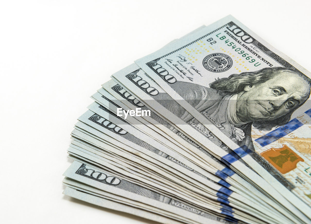 Close-Up Of American One Hundred Dollar Bills Over White Background