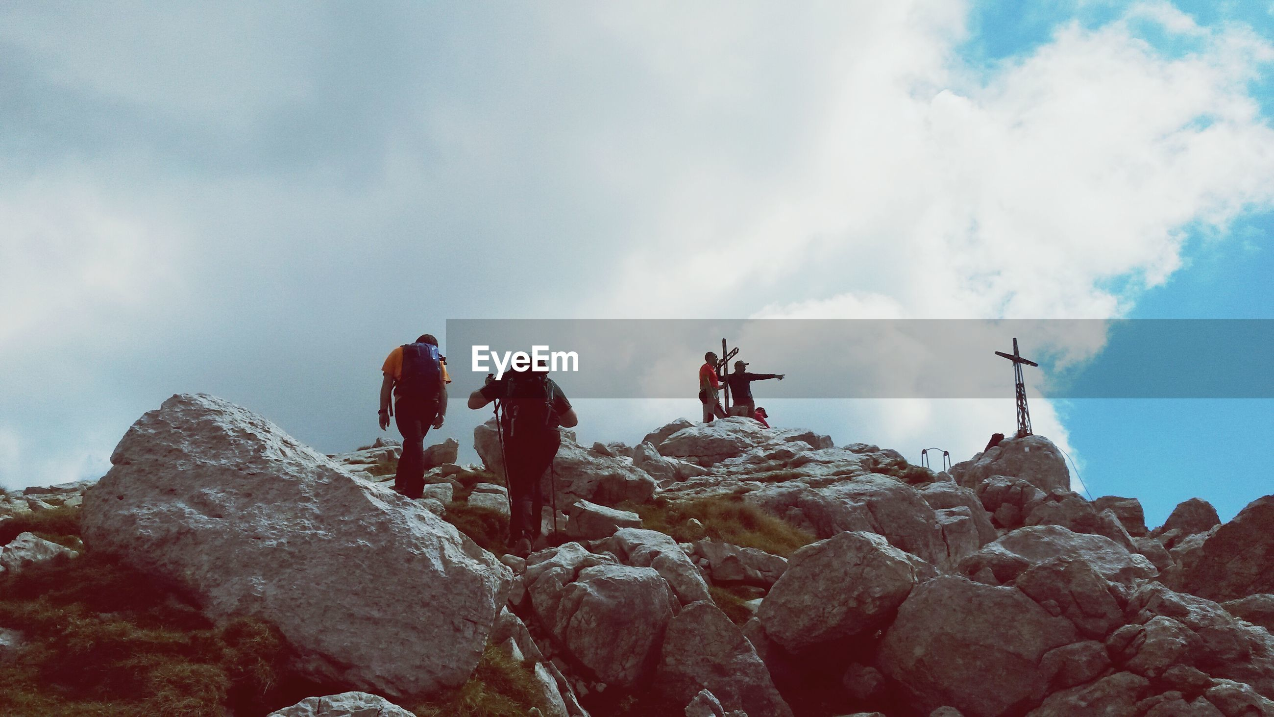 Low angle view of hikers climbing rocks