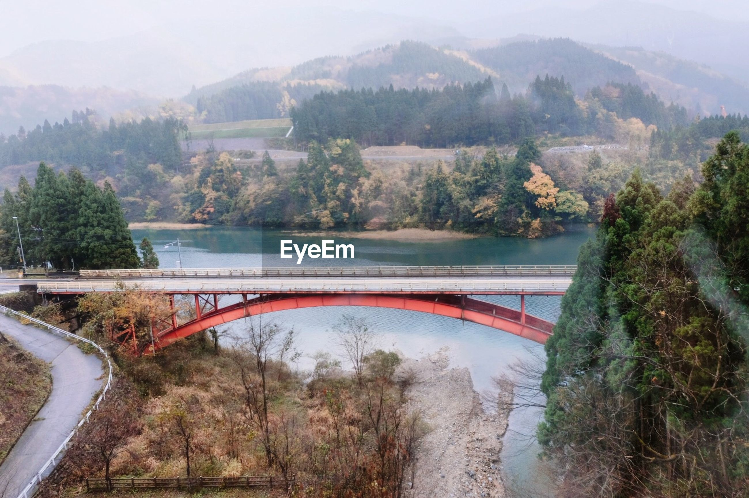 HIGH ANGLE VIEW OF BRIDGE OVER RIVER AGAINST TREES