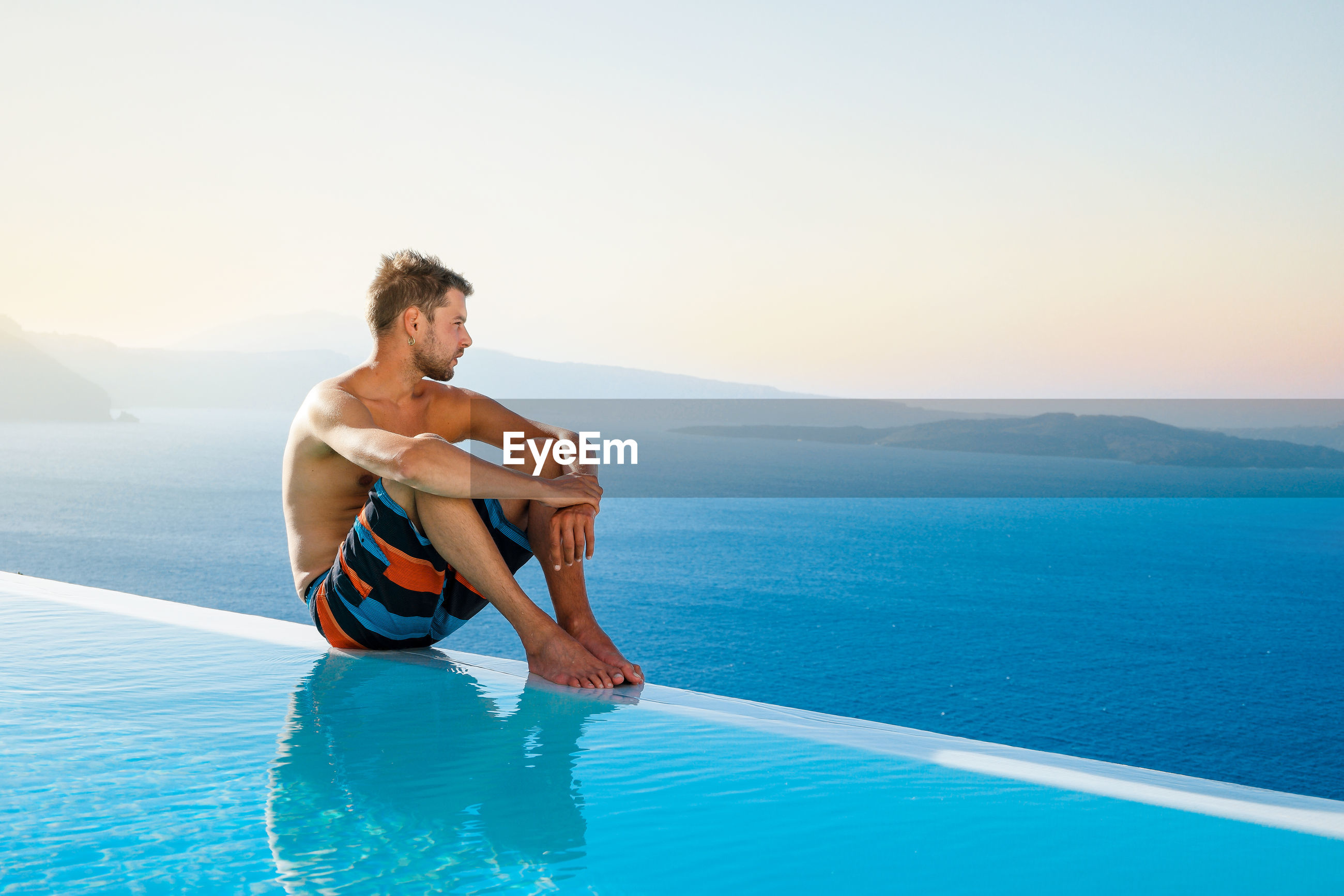 Young man sitting at poolside against sea