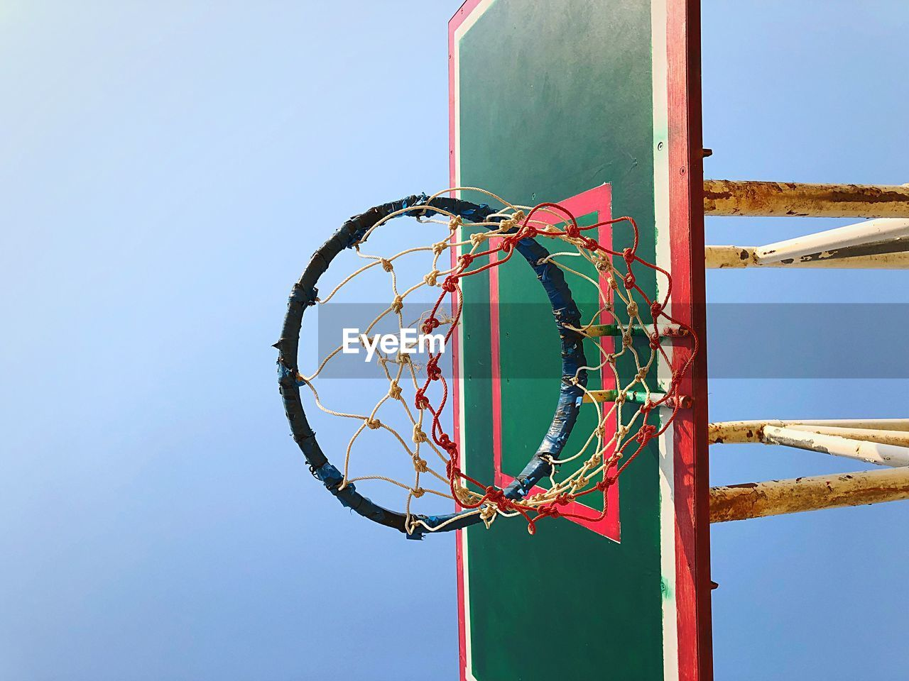 sky, clear sky, nature, day, no people, low angle view, metal, copy space, blue, outdoors, basketball - sport, net - sports equipment, shape, basketball hoop, sunlight, geometric shape, sport, art and craft, pole, built structure, directly below