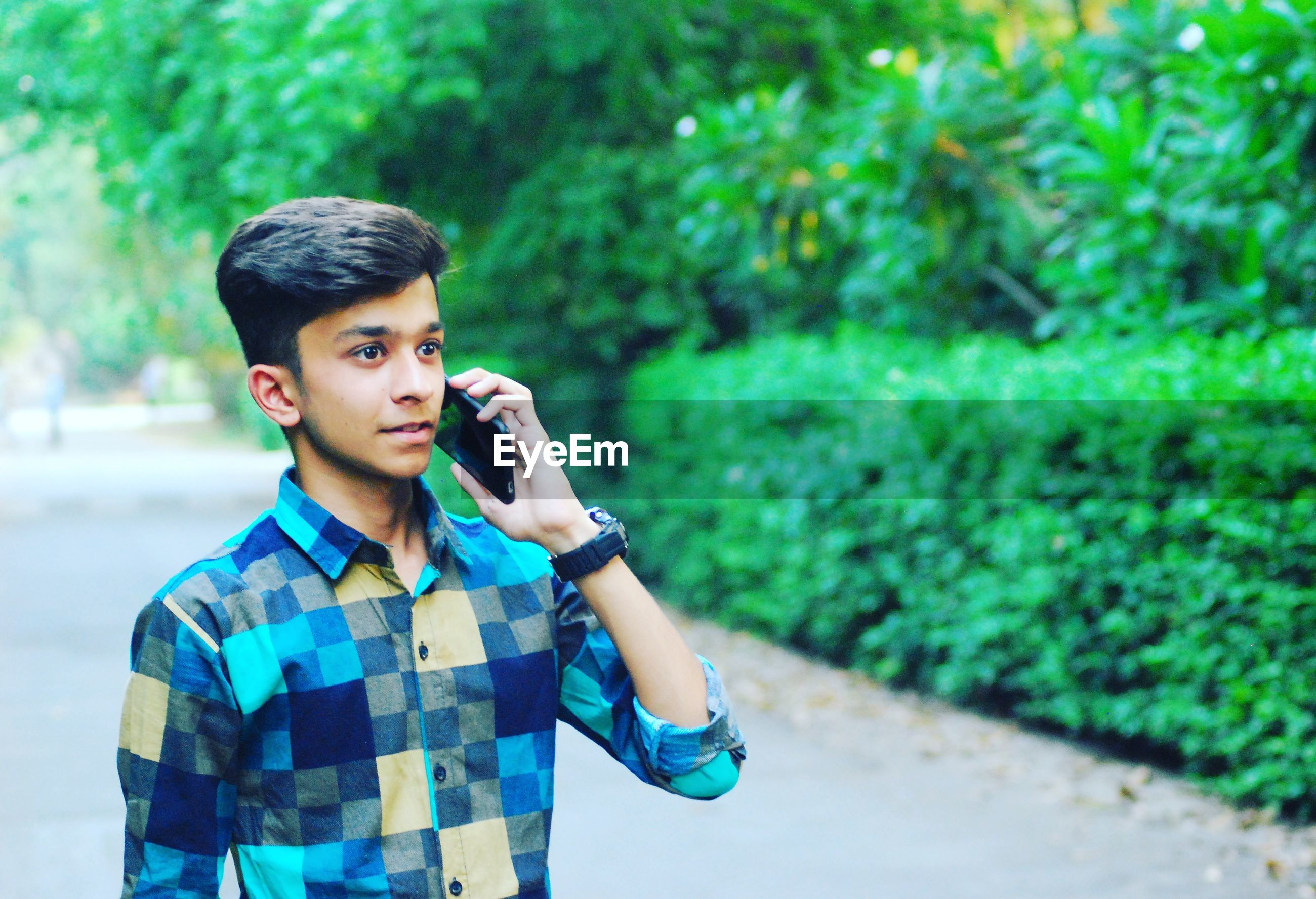 Teenage boy talking on mobile phone while standing outdoors
