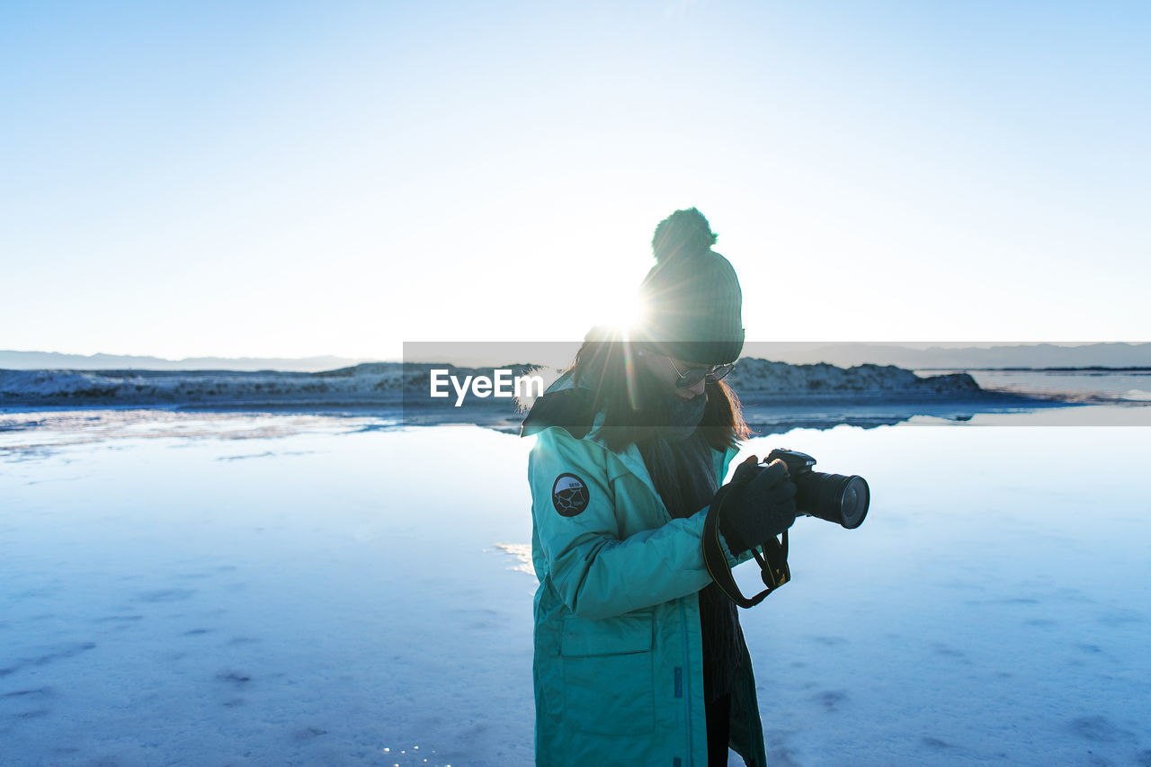 sky, water, leisure activity, photography themes, real people, lifestyles, photographing, camera - photographic equipment, nature, sea, women, activity, people, technology, beauty in nature, adult, holding, land, standing, photographer, digital camera, outdoors, warm clothing