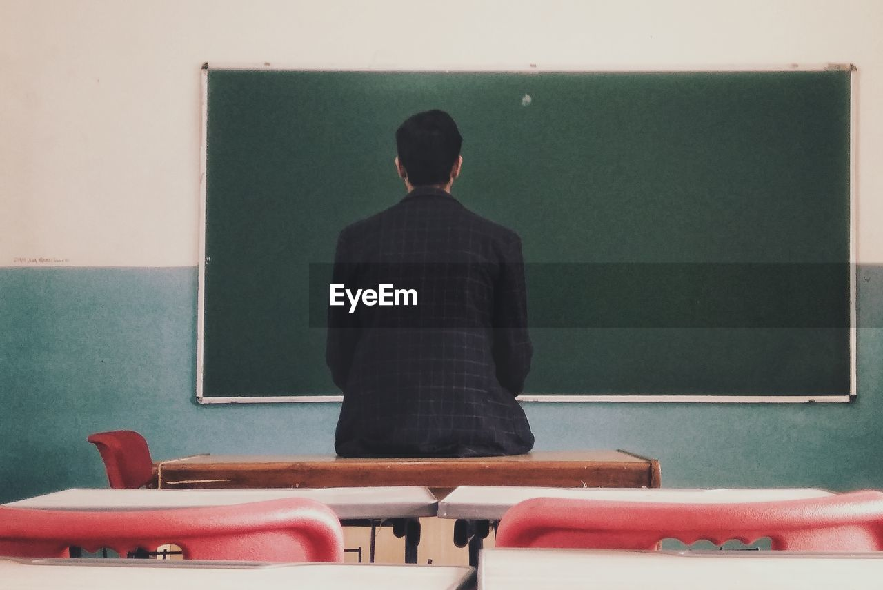 Rear view of man sitting on table looking at blackboard