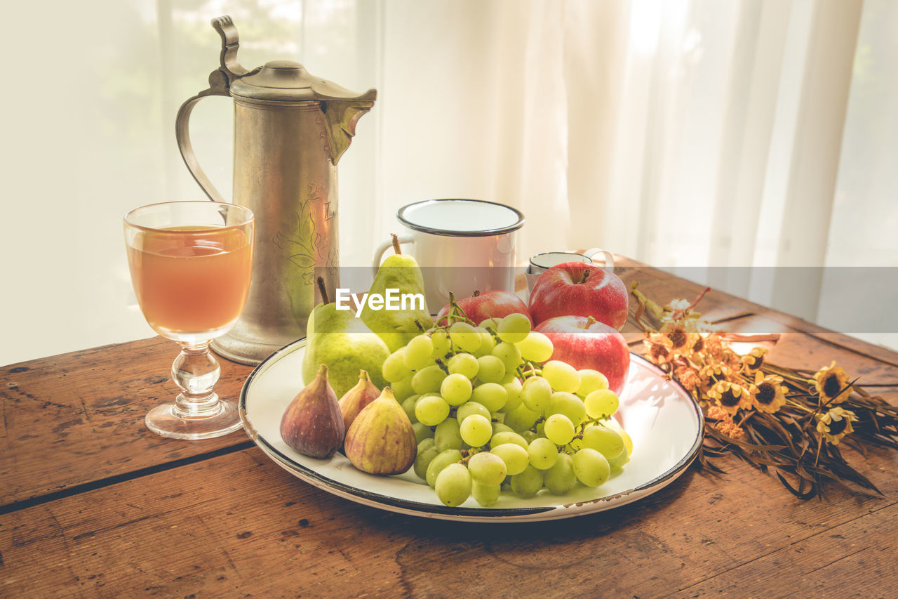 Close-Up Of Fruits And Drink On Table At Home