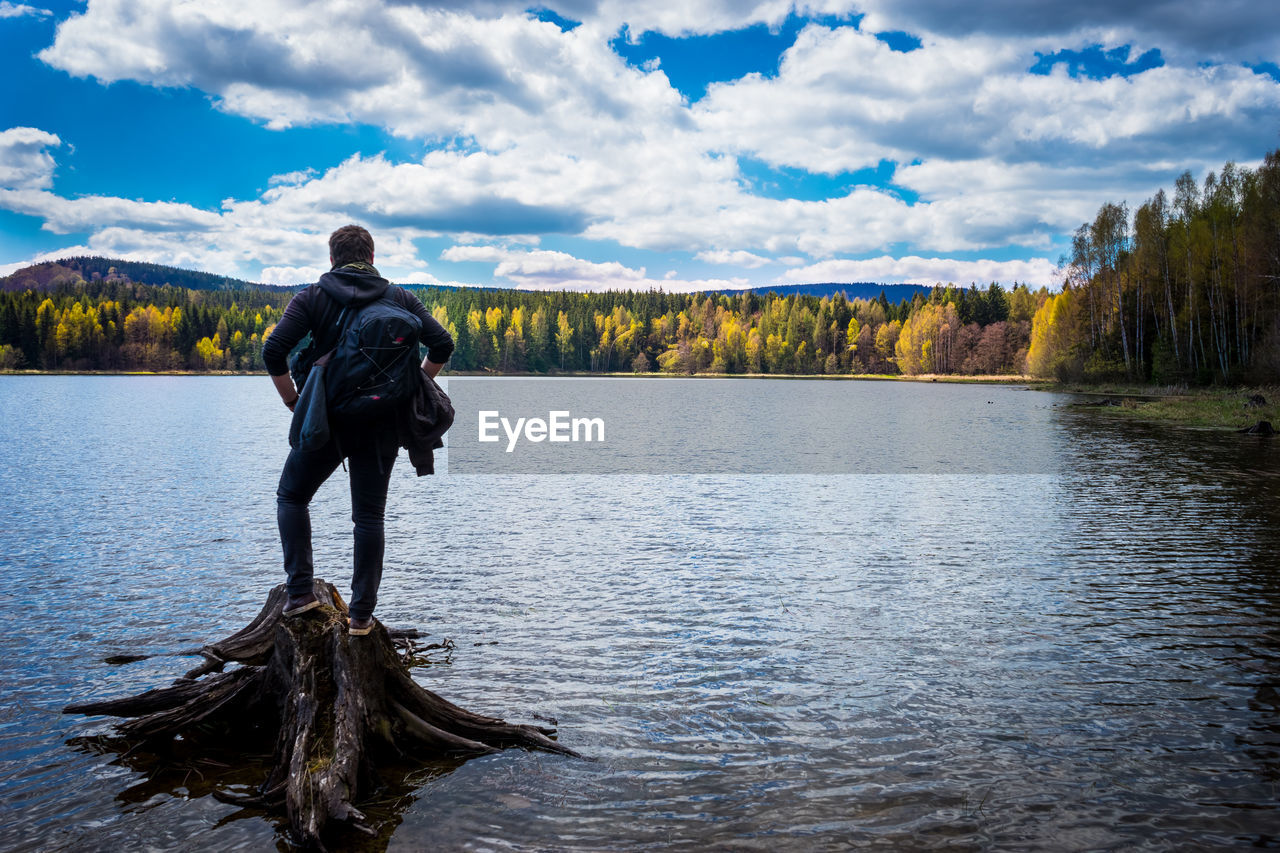 Rear view of man overlooking calm lake