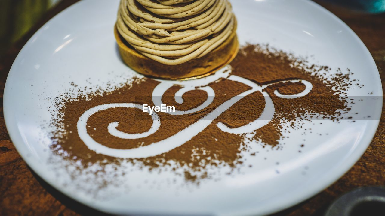 Close-Up Of Design Made On Ground Coffee By Food In Plate