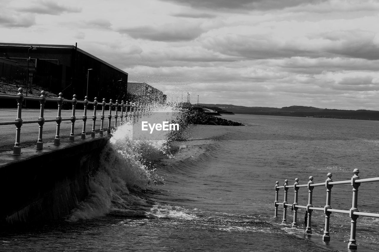 sea, water, motion, railing, outdoors, sky, force, day, no people, built structure, cloud - sky, nature, architecture, crash, beauty in nature