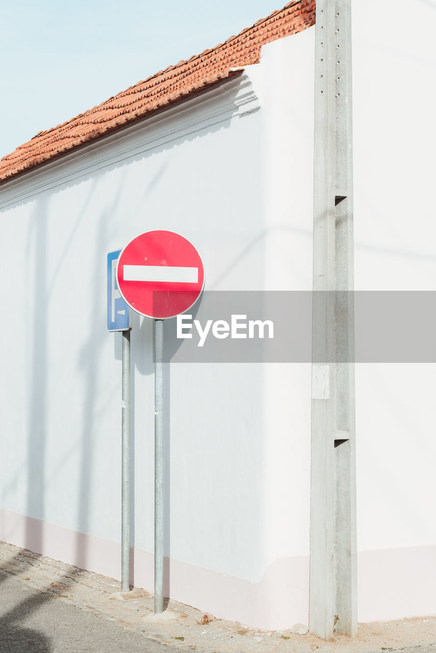 ROAD SIGN ON WALL BY BUILDING