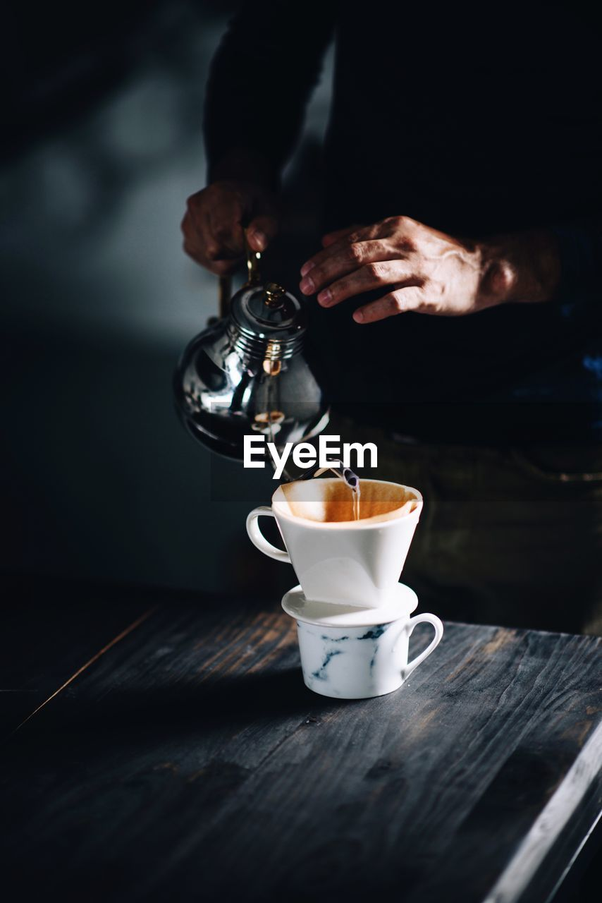 Close-Up Of Hand Pouring Coffee In Cup On Table