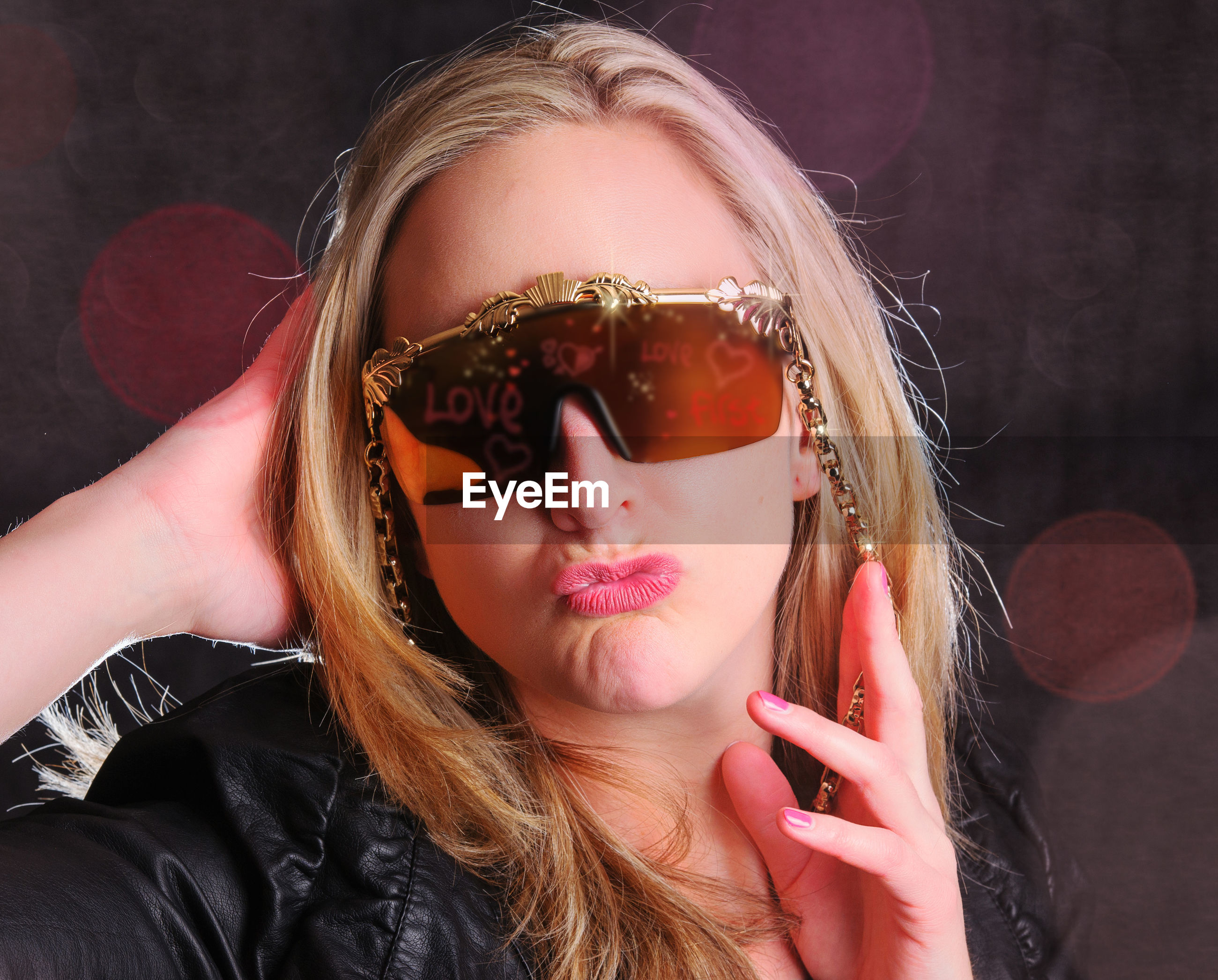 Portrait of fashionable woman wearing sunglasses while puckering