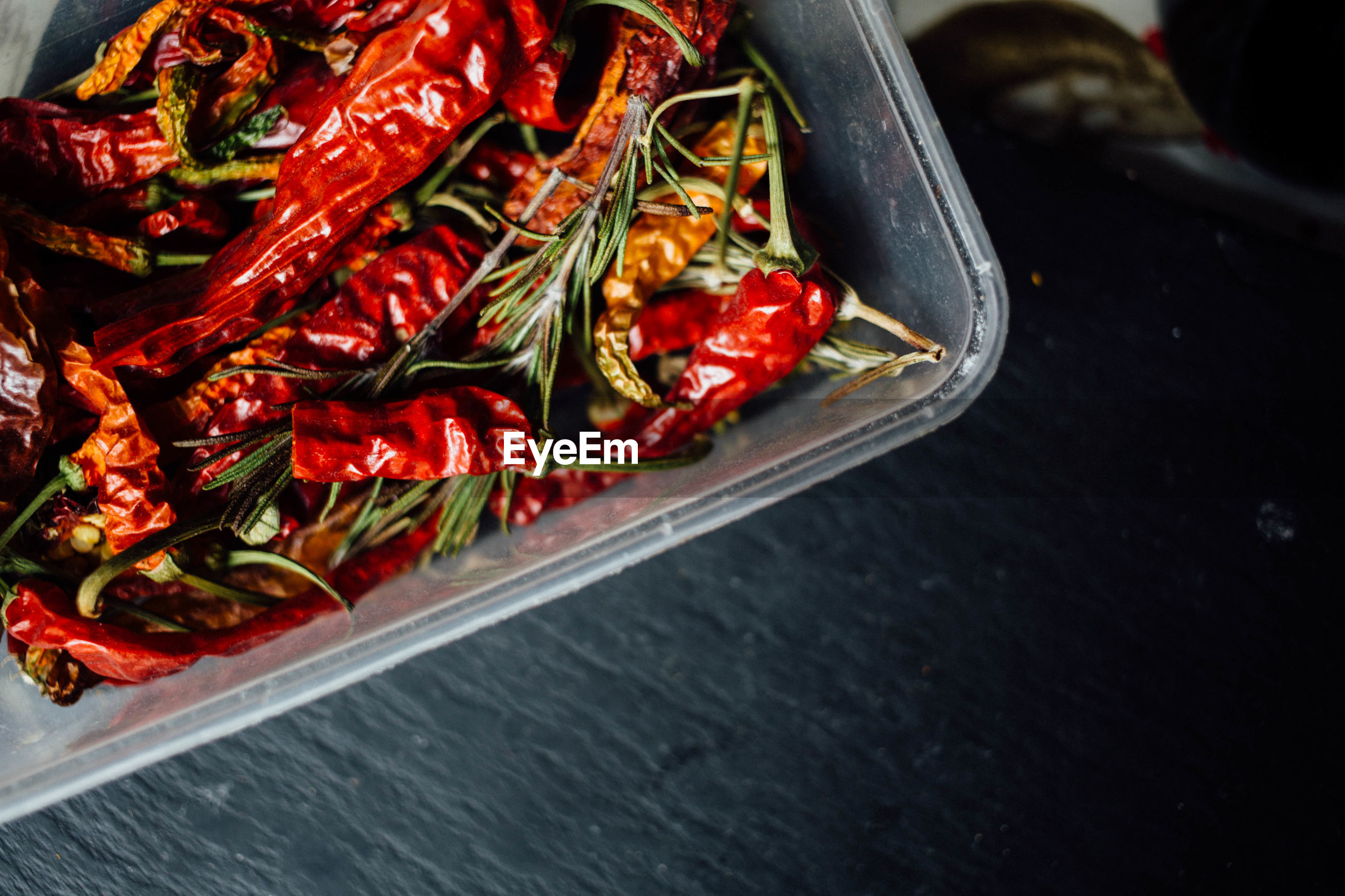 Directly above shot of red chili peppers and rosemary leaves in container on table