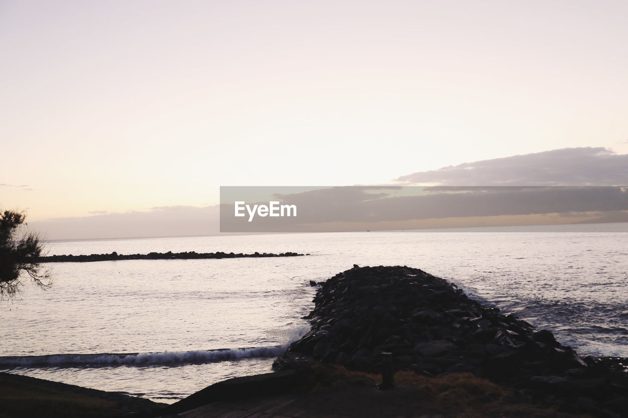 sky, water, sea, scenics - nature, beauty in nature, tranquility, tranquil scene, nature, sunset, beach, land, copy space, rock, non-urban scene, rock - object, idyllic, no people, outdoors, remote