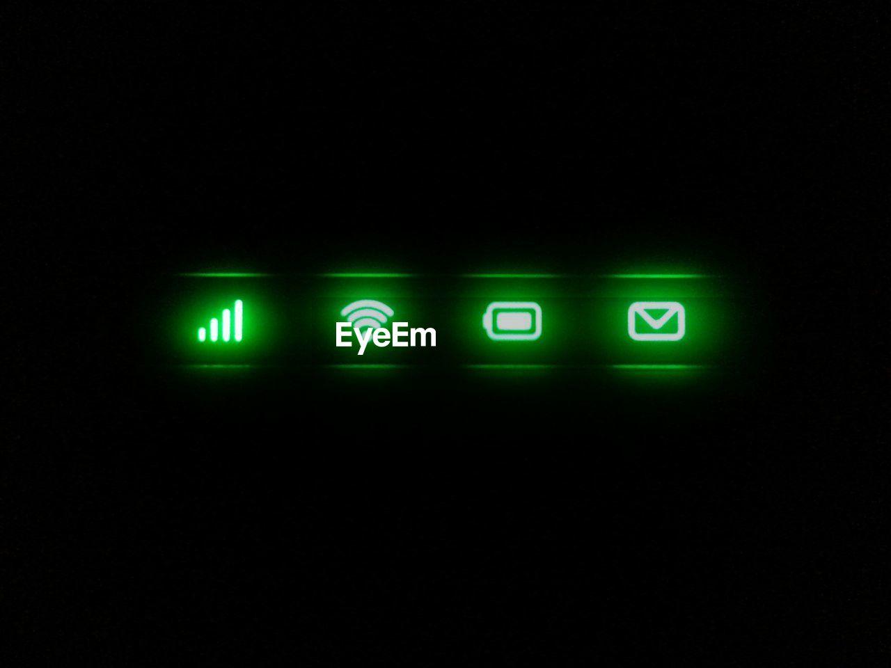 Close-Up Of Green Illuminated Icons Against Black Background