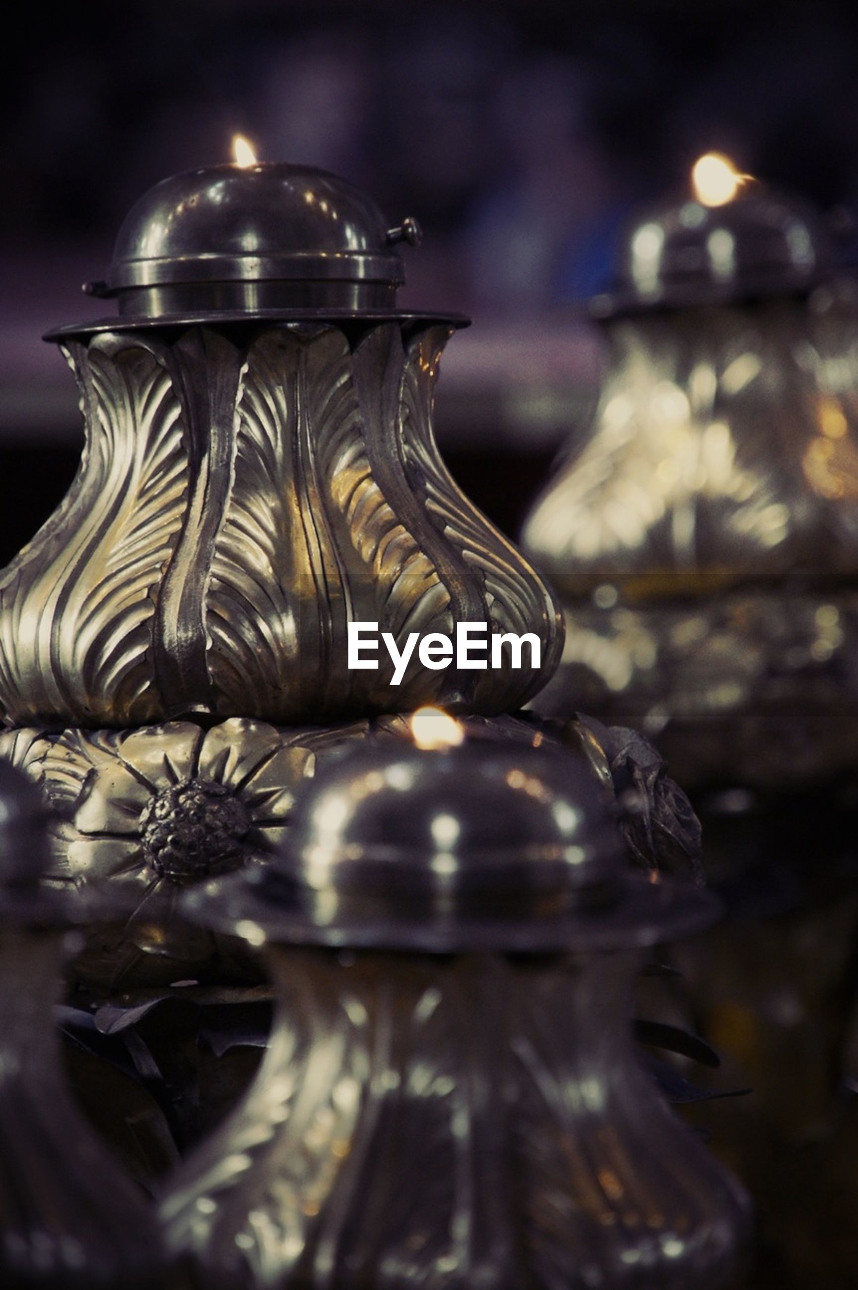 focus on foreground, close-up, religion, indoors, selective focus, spirituality, place of worship, night, art and craft, no people, metal, temple - building, ornate, illuminated, still life, decoration, old, hanging, gold colored