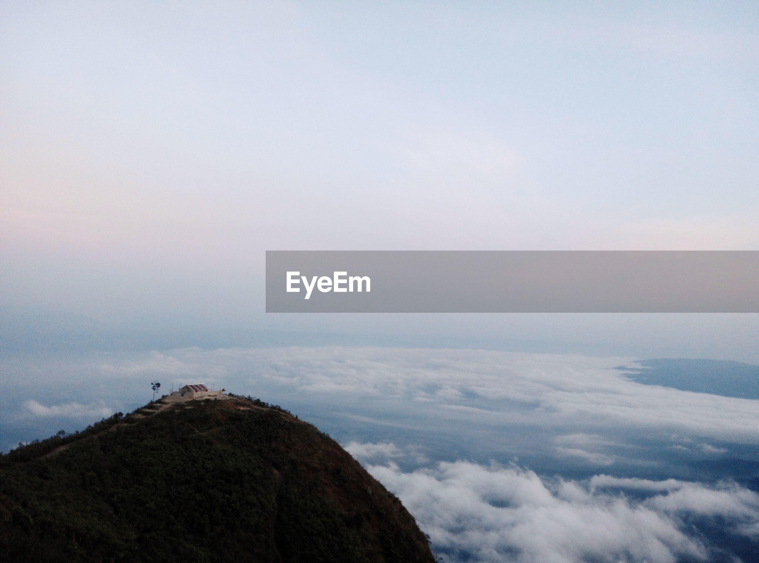Scenic view of mountain peak and clouds against sky