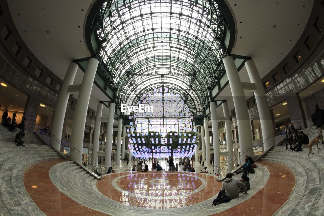 architecture, built structure, indoors, incidental people, ceiling, travel destinations, illuminated, shopping mall, modern, day, travel, group of people, tourism, flooring, real people, building, pattern, arch, architectural column, luxury, tiled floor