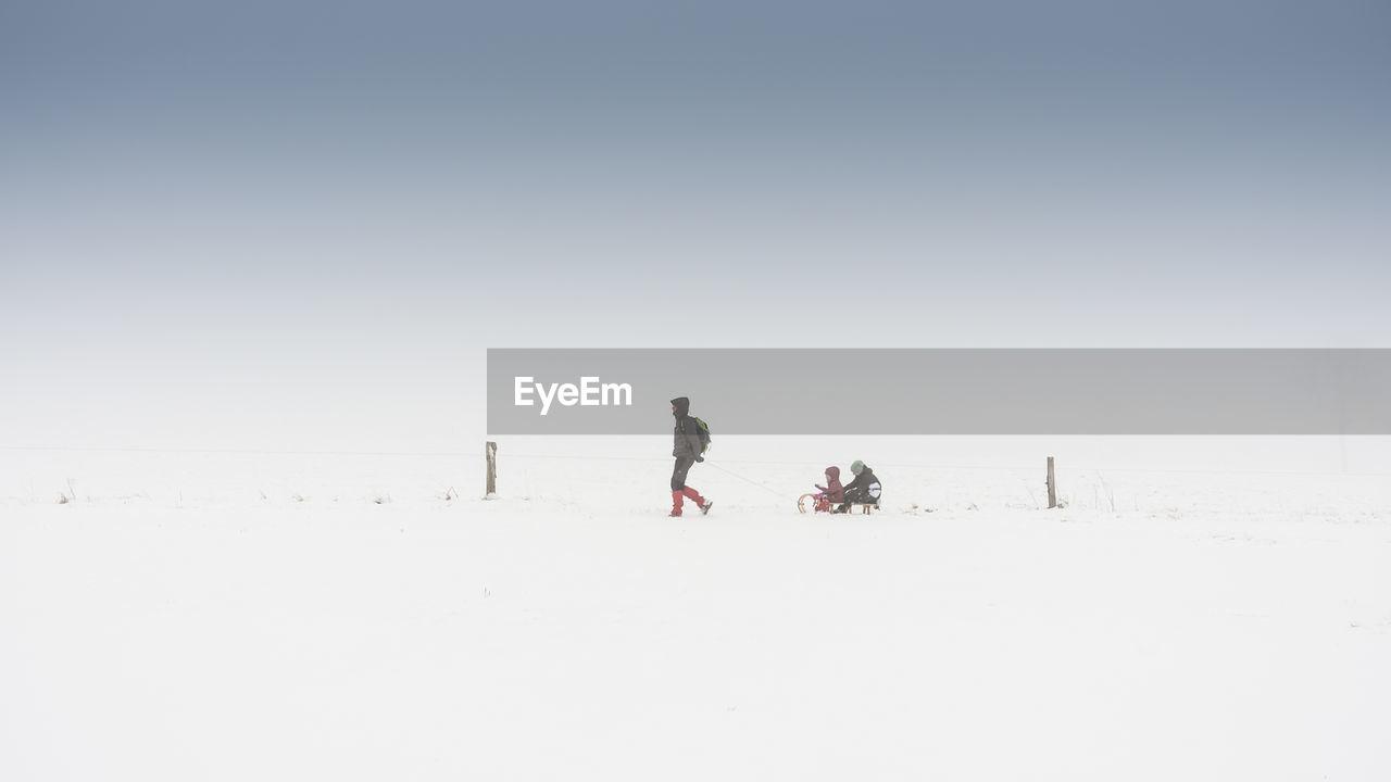 Man pulling family on sled against sky