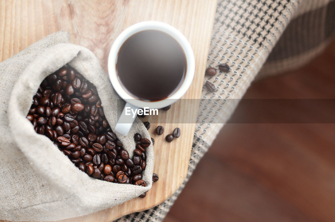food and drink, coffee, coffee - drink, freshness, cup, refreshment, drink, roasted coffee bean, food, table, still life, mug, coffee cup, indoors, wood - material, high angle view, brown, no people, close-up, coffee bean, caffeine, non-alcoholic beverage