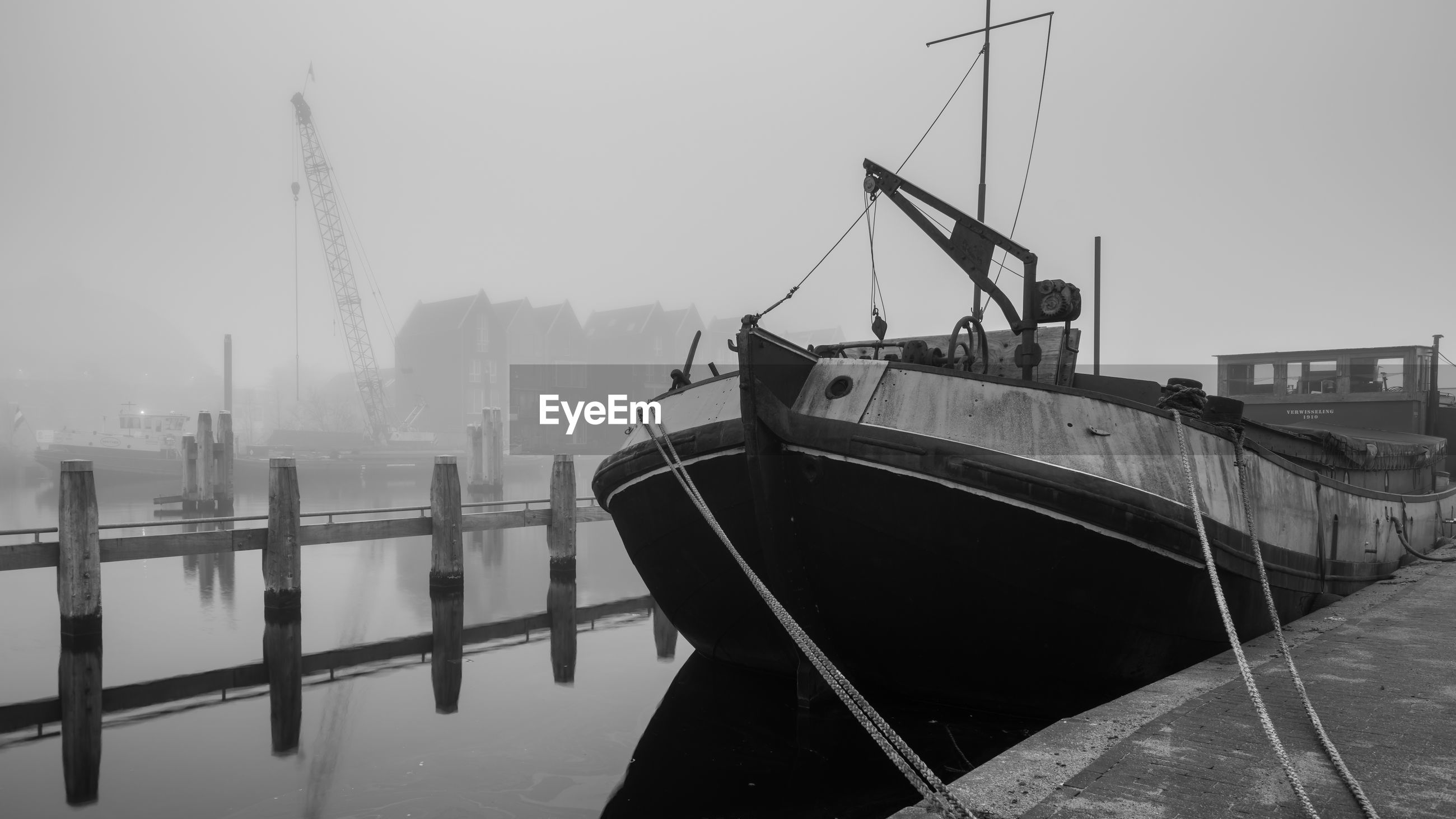 Boat moored on lake during foggy weather