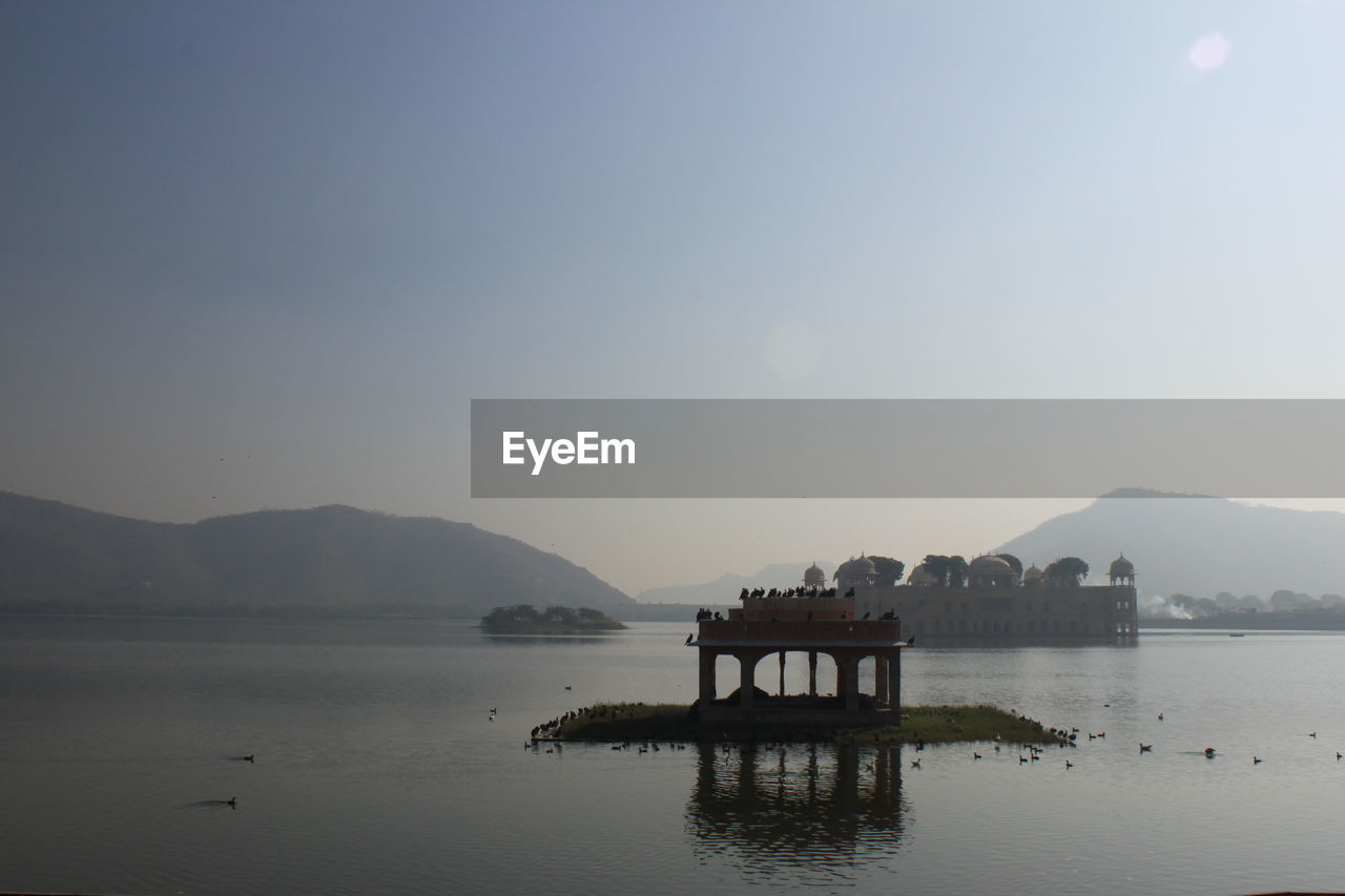 water, sky, mountain, lake, beauty in nature, scenics - nature, architecture, nature, waterfront, tranquility, no people, tranquil scene, reflection, mountain range, built structure, copy space, clear sky, non-urban scene, building exterior, outdoors