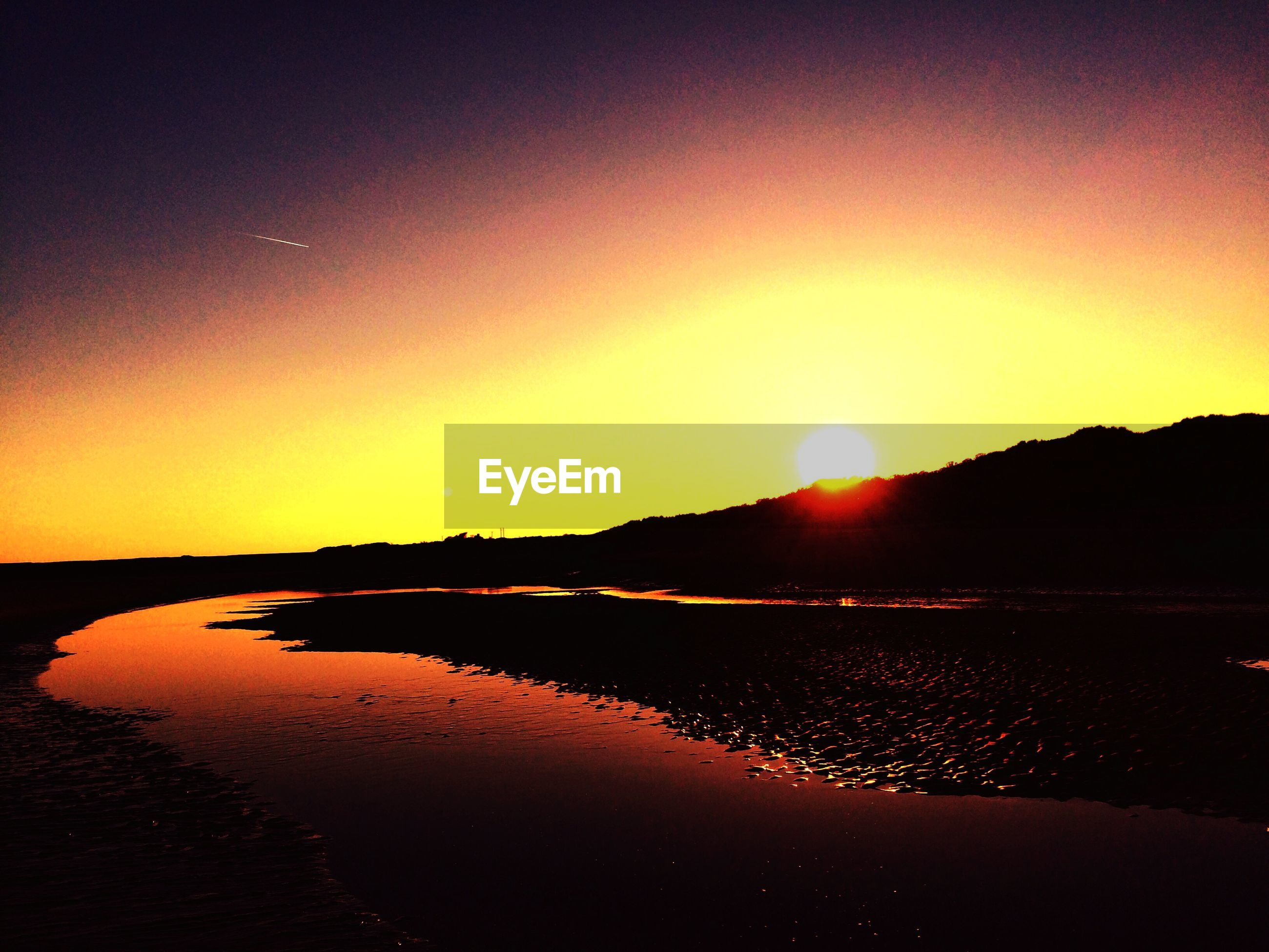 Scenic view of burry port beach against orange sky during sunset