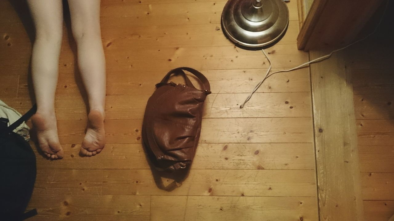 Low section of woman relaxing on hardwood floor at home