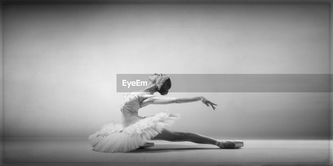dancing, ballet, full length, ballet dancer, skill, performance, indoors, one person, balance, elegance, arts culture and entertainment, tutu, women, young adult, females, copy space, studio shot, flexibility, ballet studio, stage, human arm, teenager, arms raised
