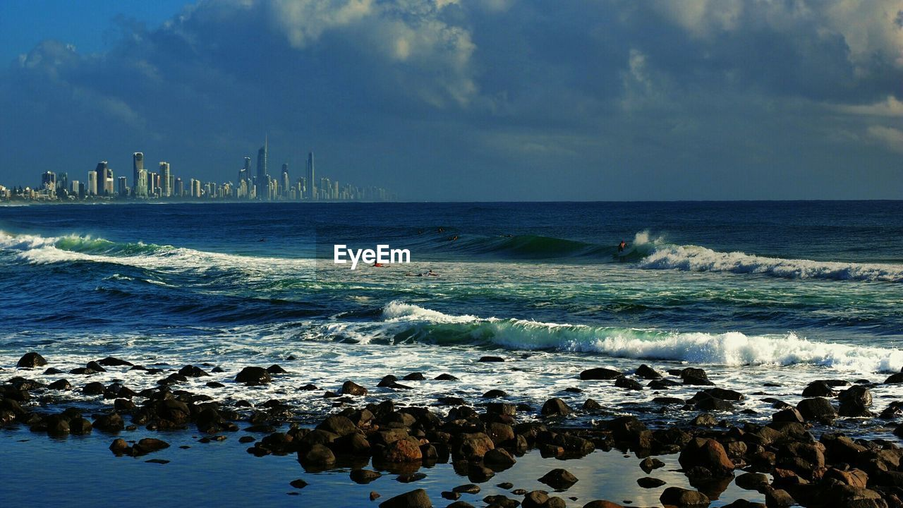 Scenic View Of Waves Rushing Towards Shore Against Cloudy Sky At Burleigh Heads