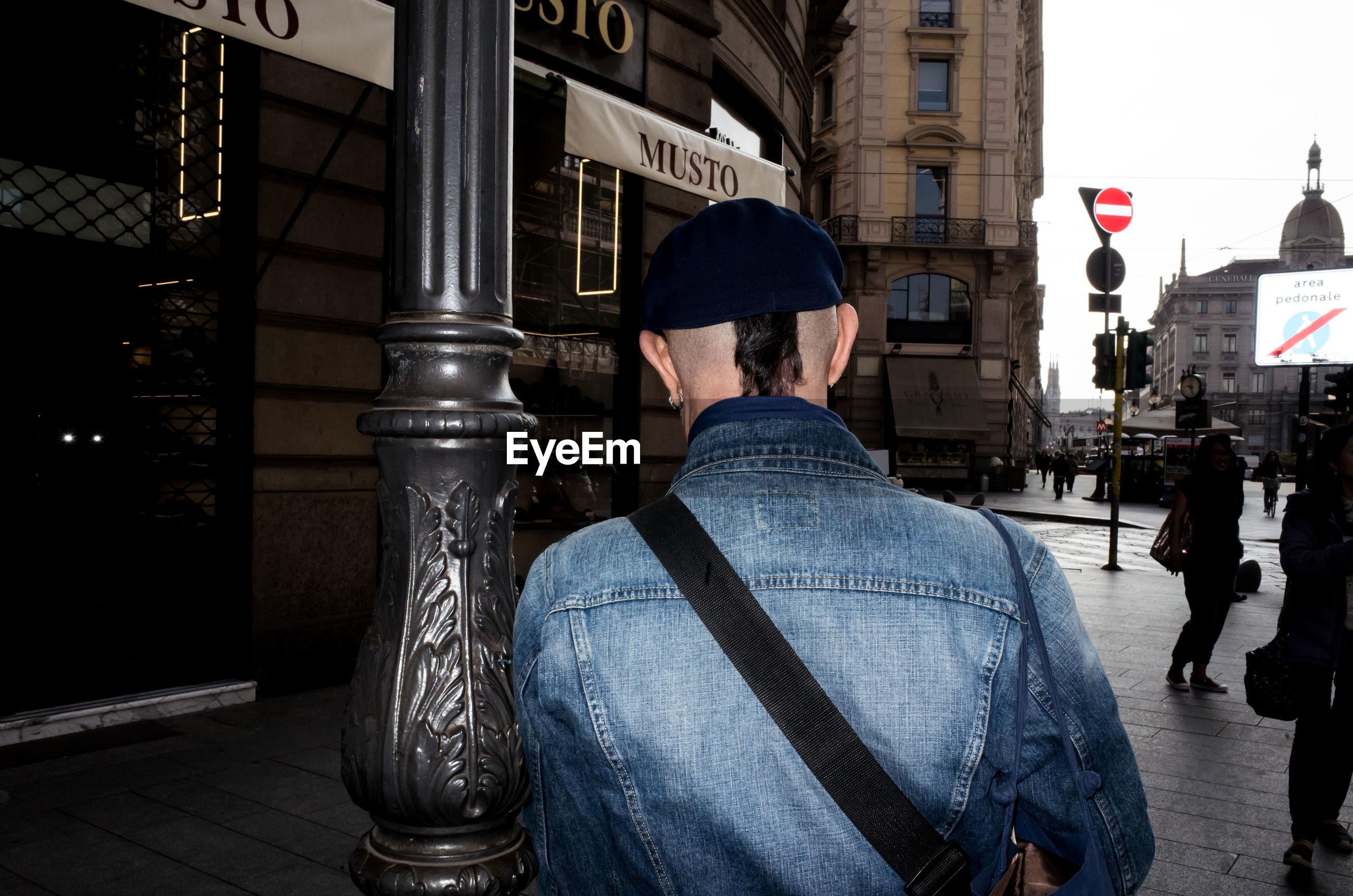 REAR VIEW OF MAN WALKING IN CITY