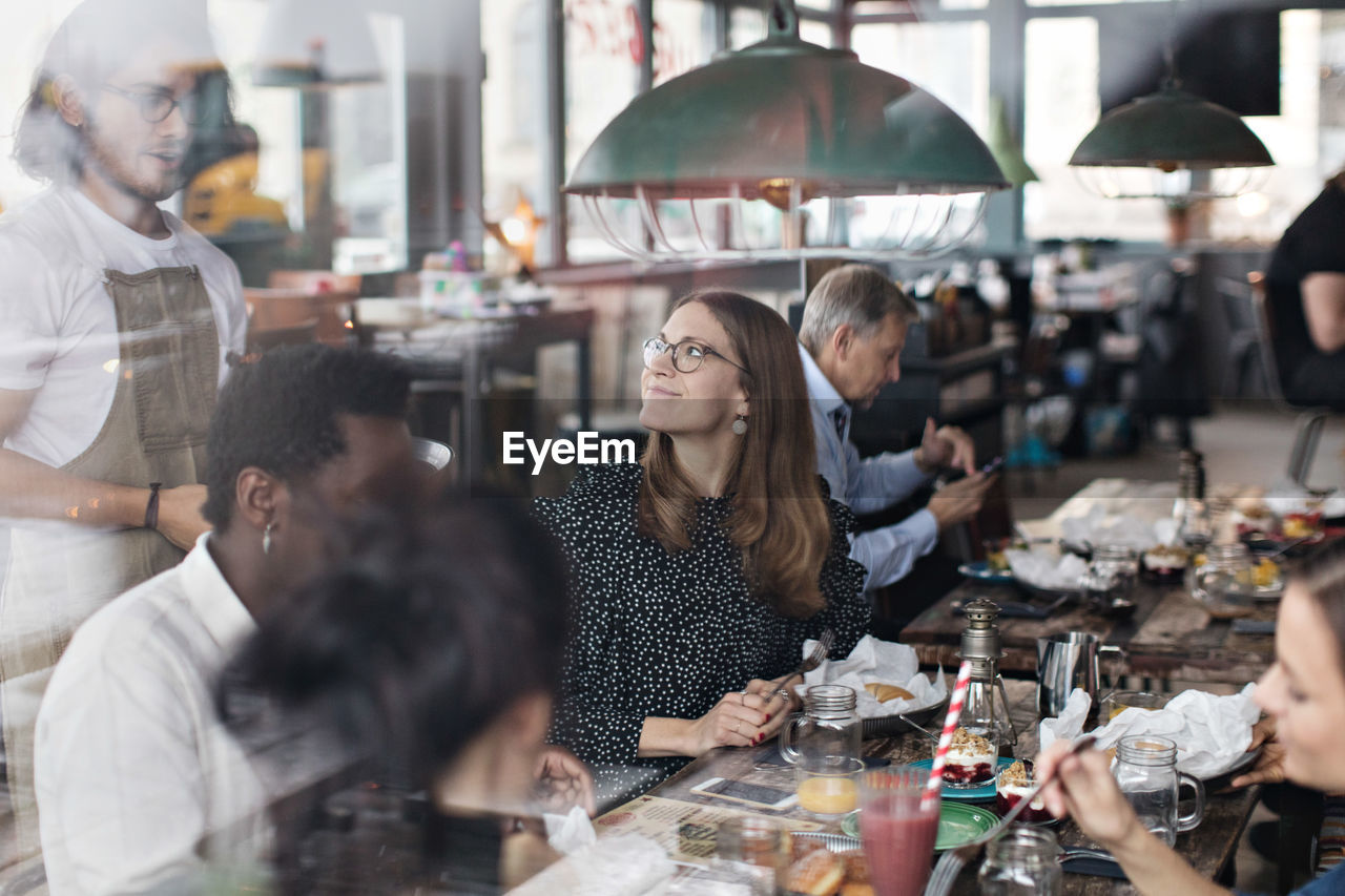 group of people, women, adult, food and drink, business, men, real people, table, restaurant, medium group of people, food, group, crowd, lifestyles, young adult, mid adult, young men, young women, people, incidental people, glass