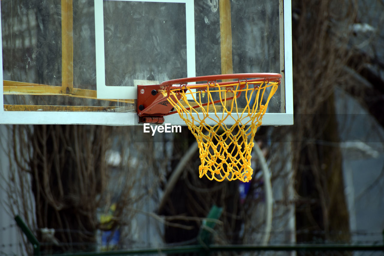 LOW ANGLE VIEW OF BASKETBALL HOOP AGAINST THE WALL