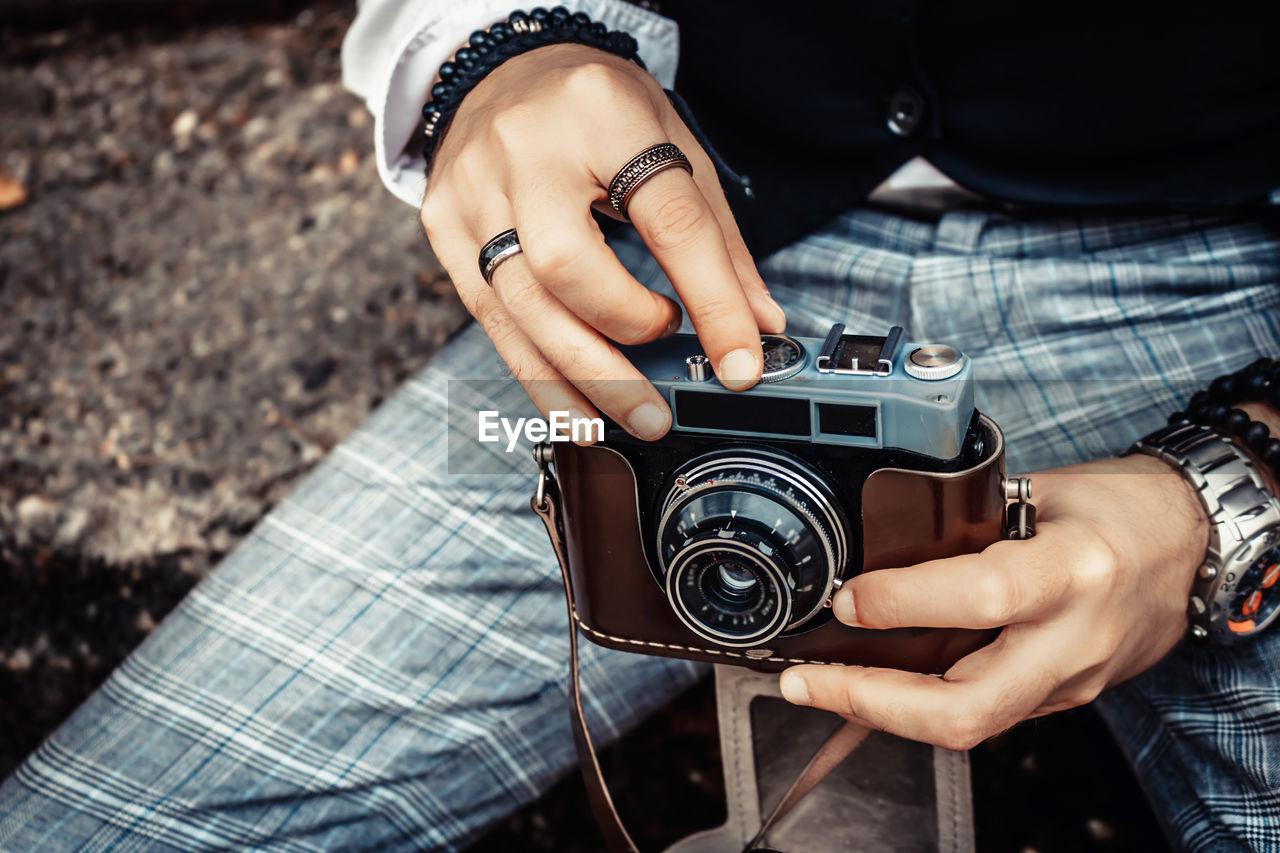 Close-up of photographer using analog photo camera.
