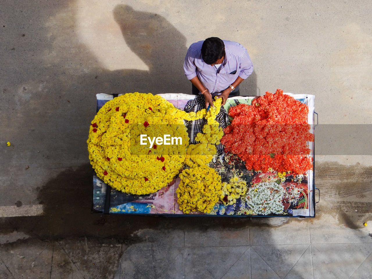 High Angle View Of Man Preparing Flower Garland On Roadside In City